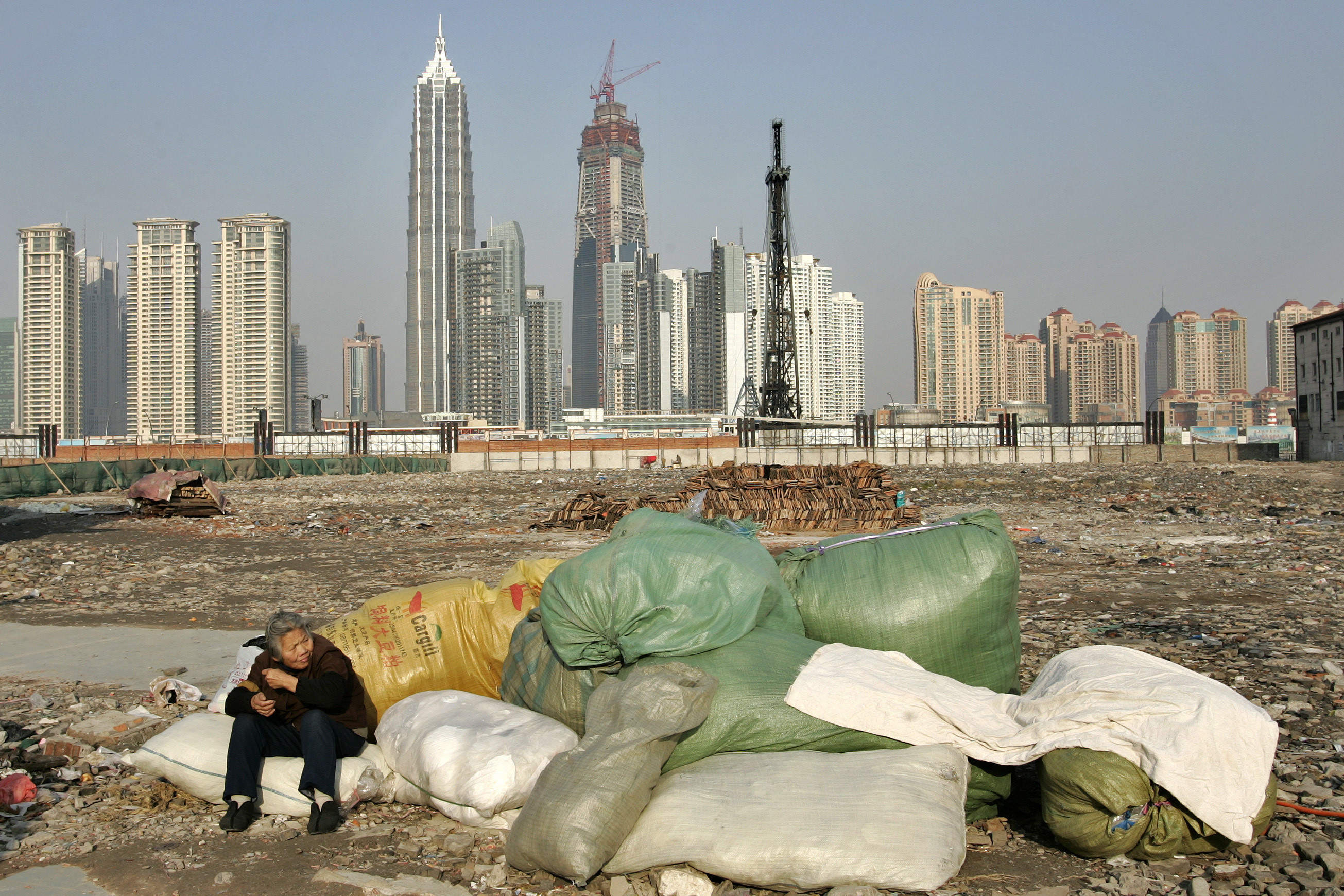 A garbage collector rests at a demolished housing area in Shanghai January 7, 2007. A report by the Chinese Academy of Social Sciences (CASS) shows that China's worrisome income gap is showing no signs of narrowing despite government efforts to bridge it,  Xinhua News Agency reported.  REUTERS/Aly Song (CHINA) - GM1DUIHQNVAA
