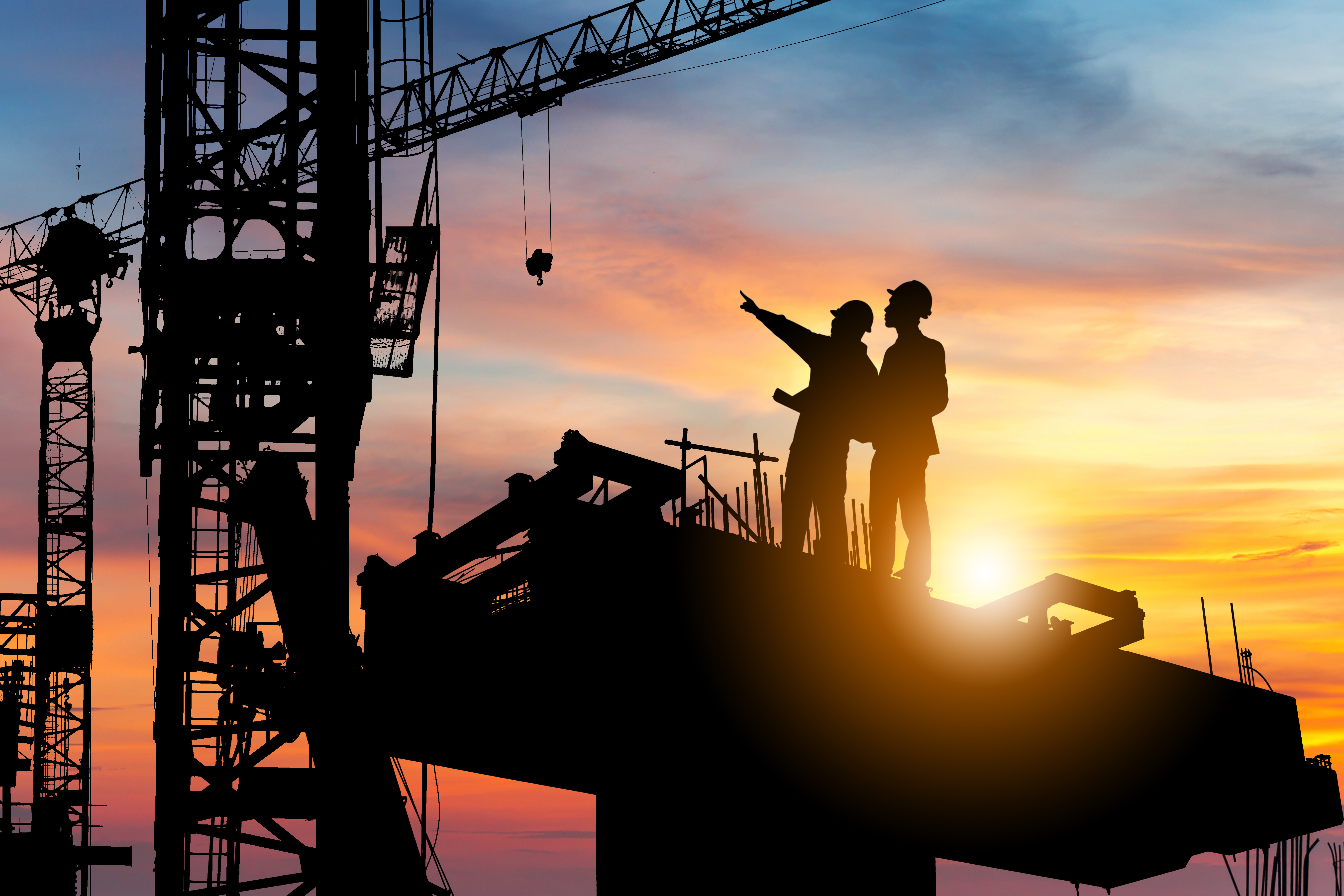 Silhouette of engineer and worker checking project at building site. Image: JooFotia/Shutterstock
