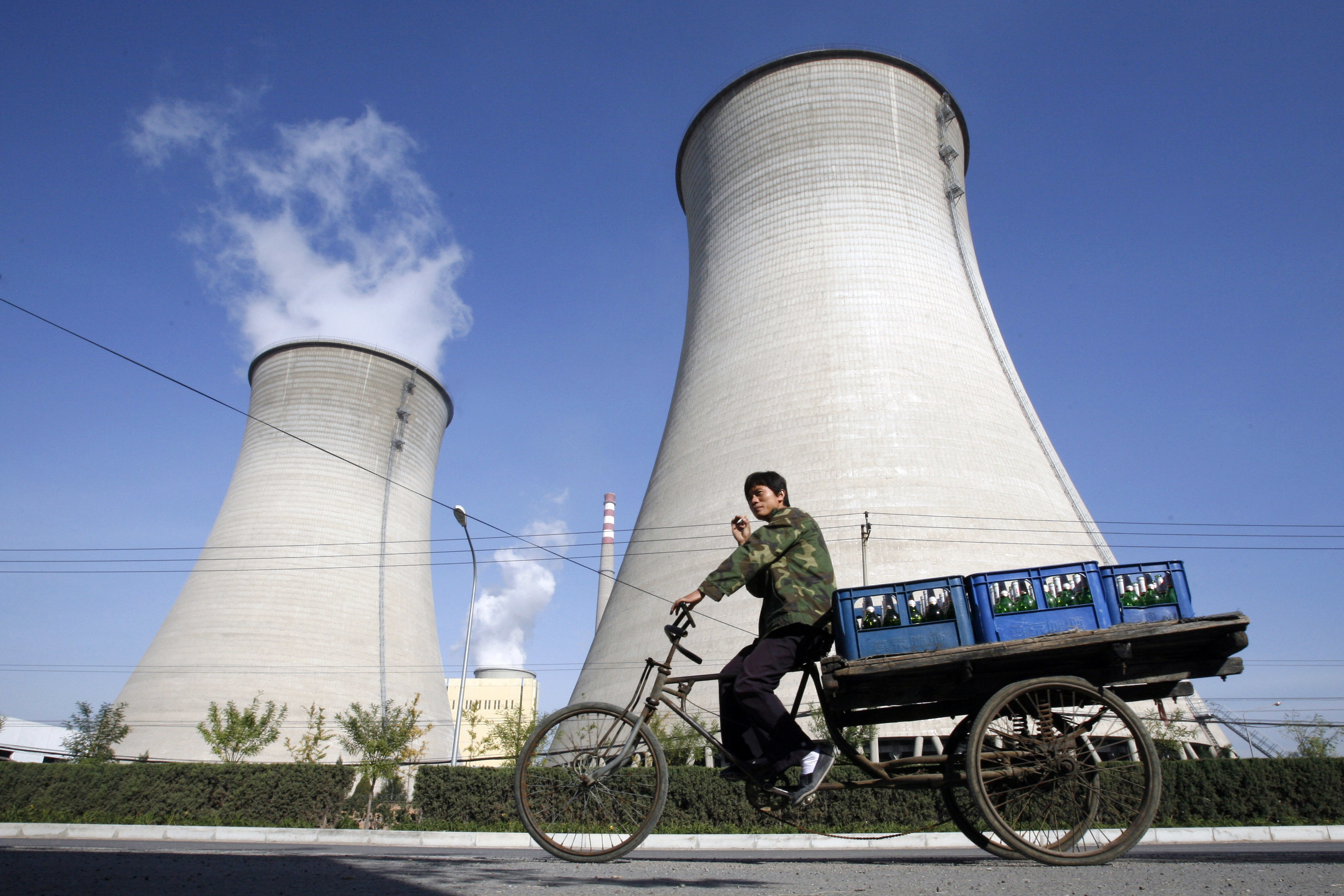 A worker drives his tricycle in front of a power plant on the outskirts of Beijing October