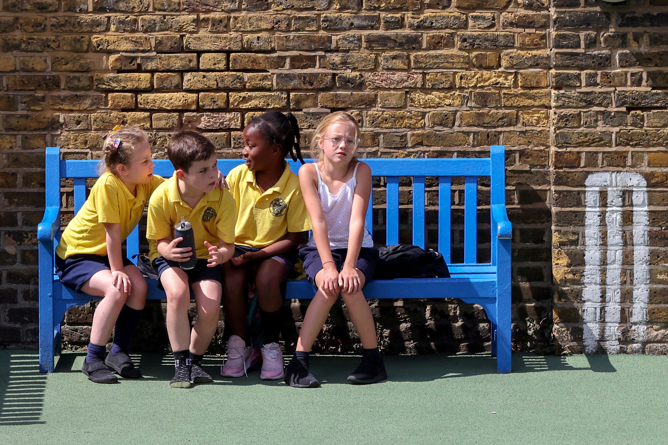Children sit on a bench in the playground at St John's Primary School in Fulham amid the spread of the coronavirus disease (COVID-19) in London, Britain July 16, 2020.      REUTERS/Kevin Coombs     TPX IMAGES OF THE DAY - RC2FUH9H3MMV