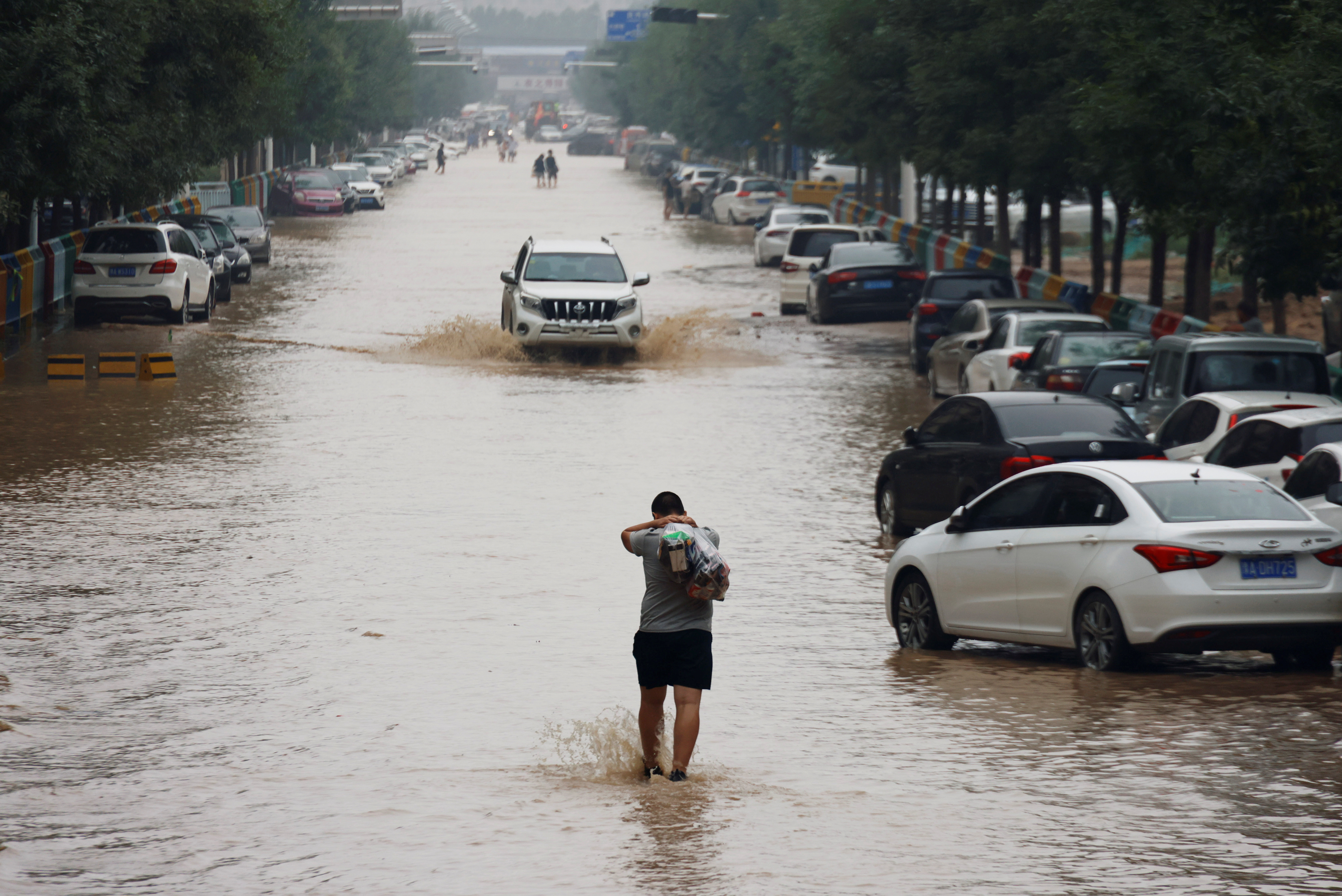 a man wades through a flooded road following heavy rainfall in Zhengzhou, Henan province, China July 23, 2021