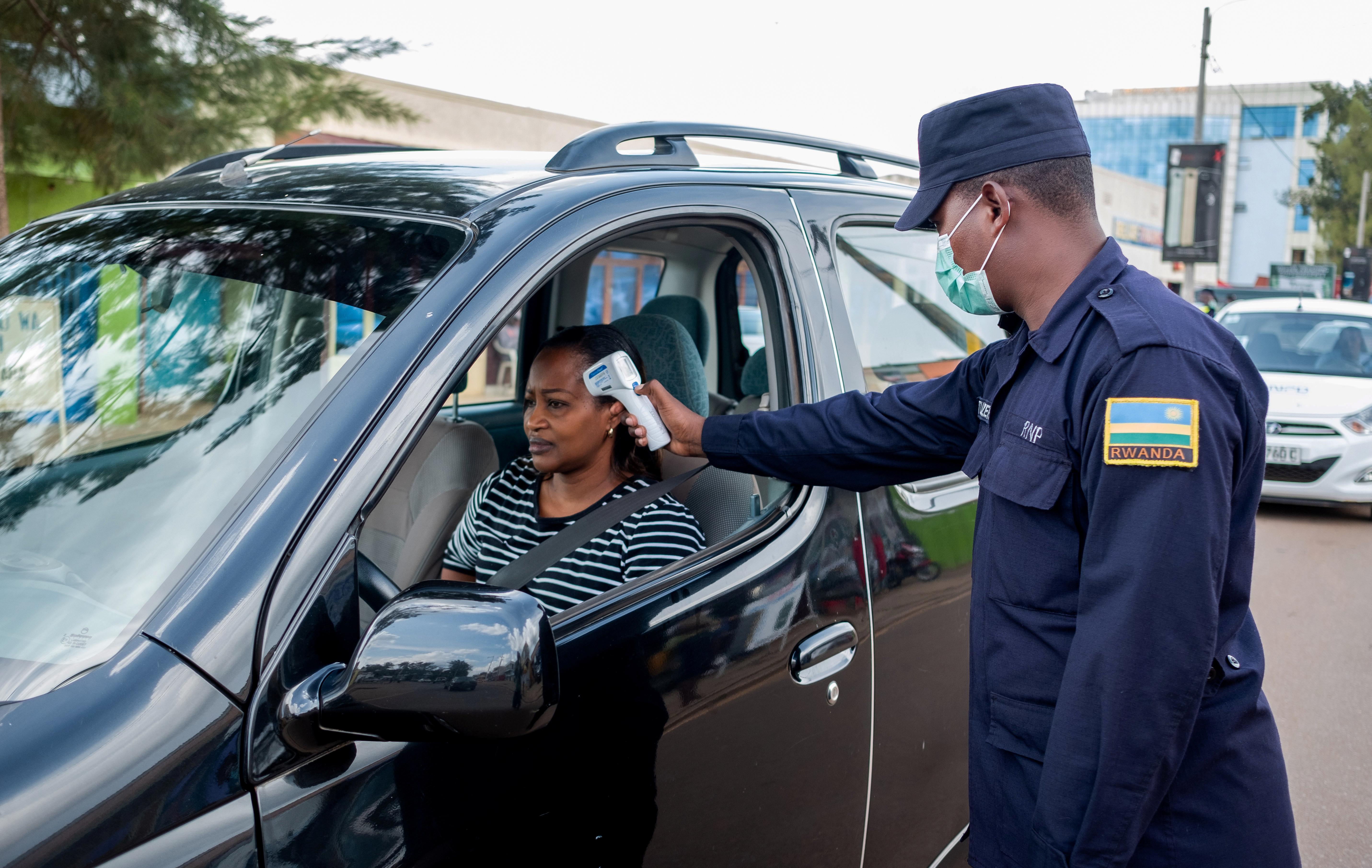 A Rwandan police checks the temperature of a motorist as he enforces a lockdown to stem the coronavirus disease (COVID-19) outbreak in Kigali, Rwanda April 15, 2020. Picture taken April 15, 2020. REUTERS/Jean Bizimana - RC286G9BGM1U