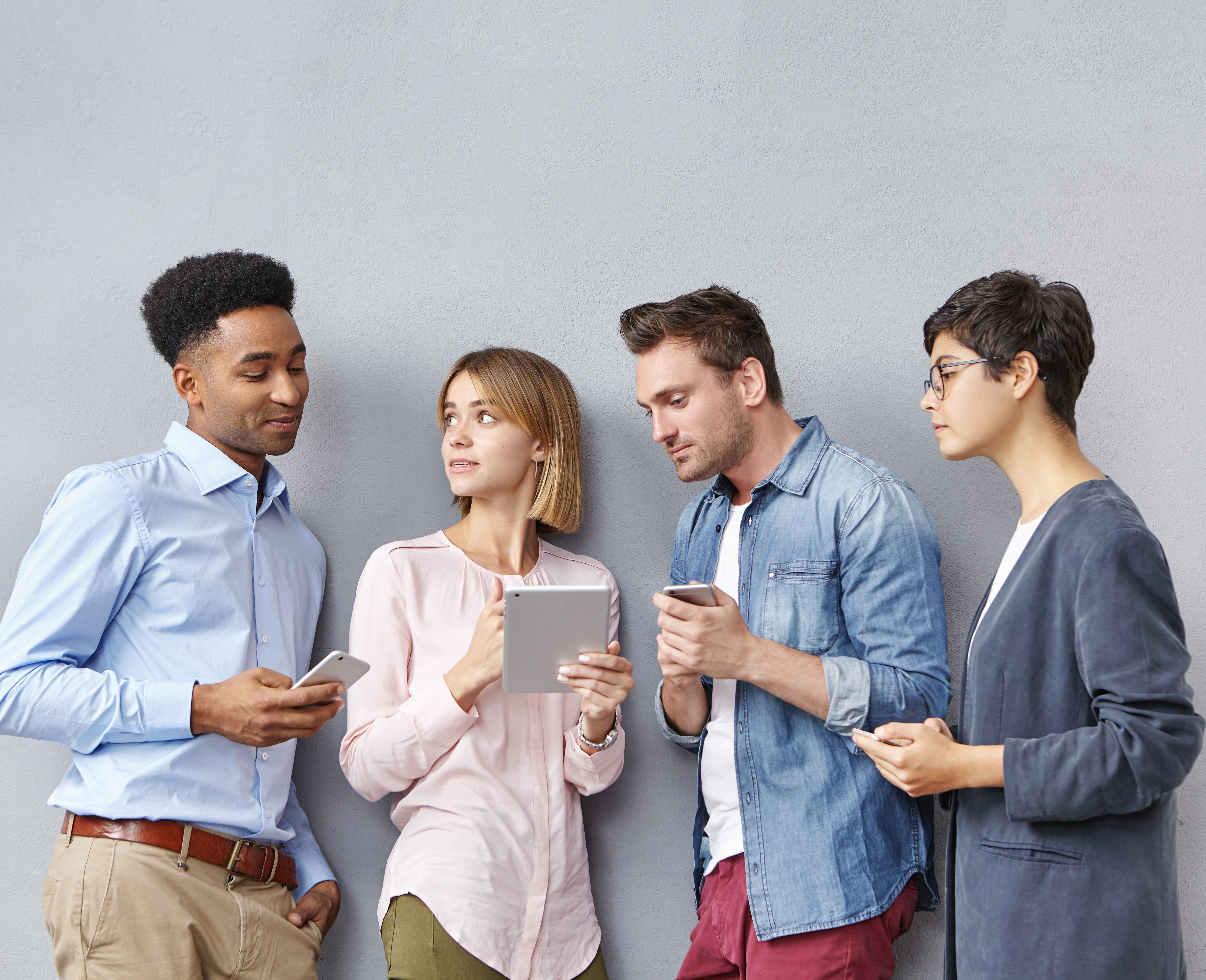 Modern education, business, startup, friendship and teamwork concept. International team of diverse ambitious talented young people standing in line in studio, using electronic gadgets and talking