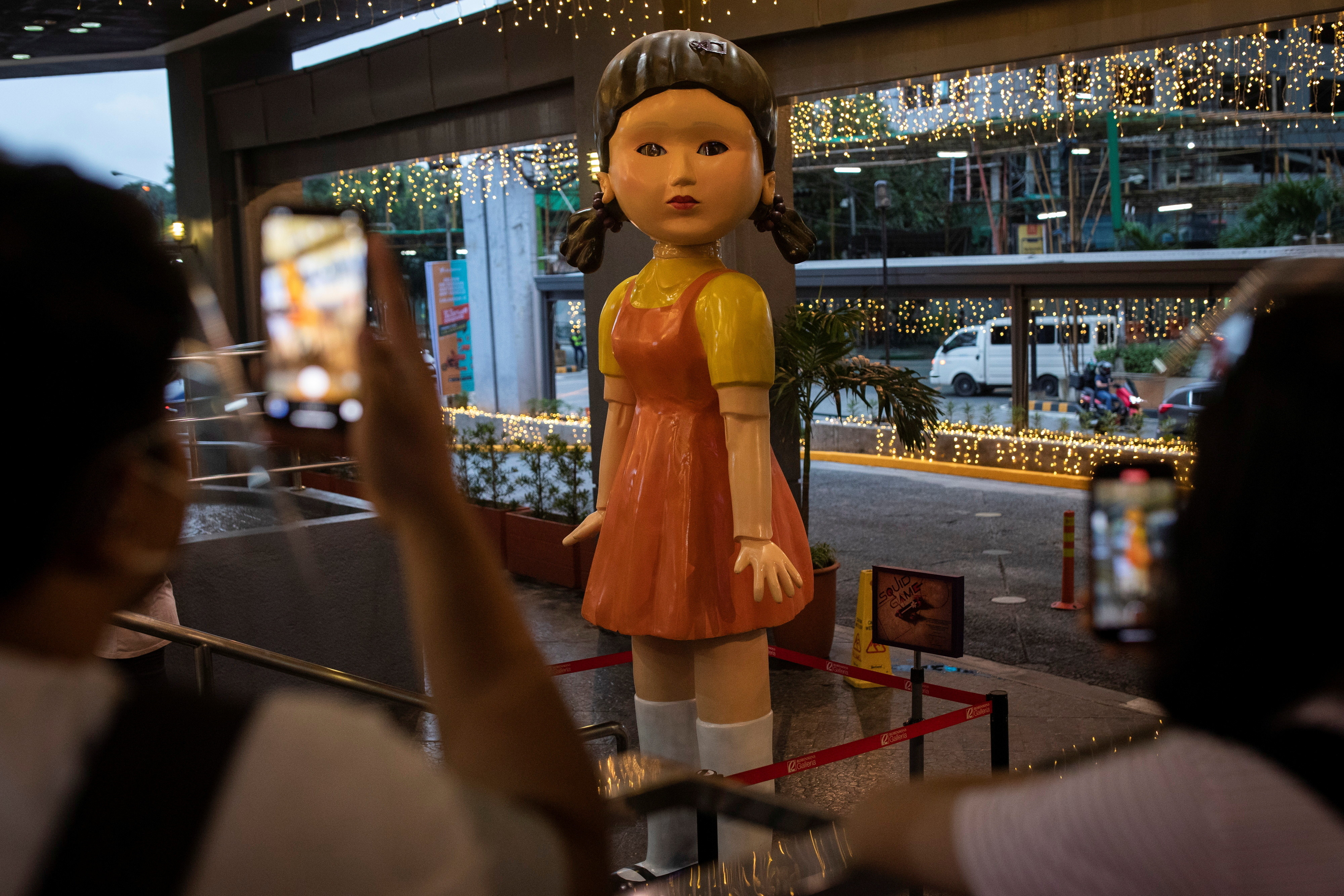"""People take pictures of the 3-metre (10 ft) tall doll from Netflix series """"Squid Game"""" displayed outside a mall in Quezon City, Philippines"""