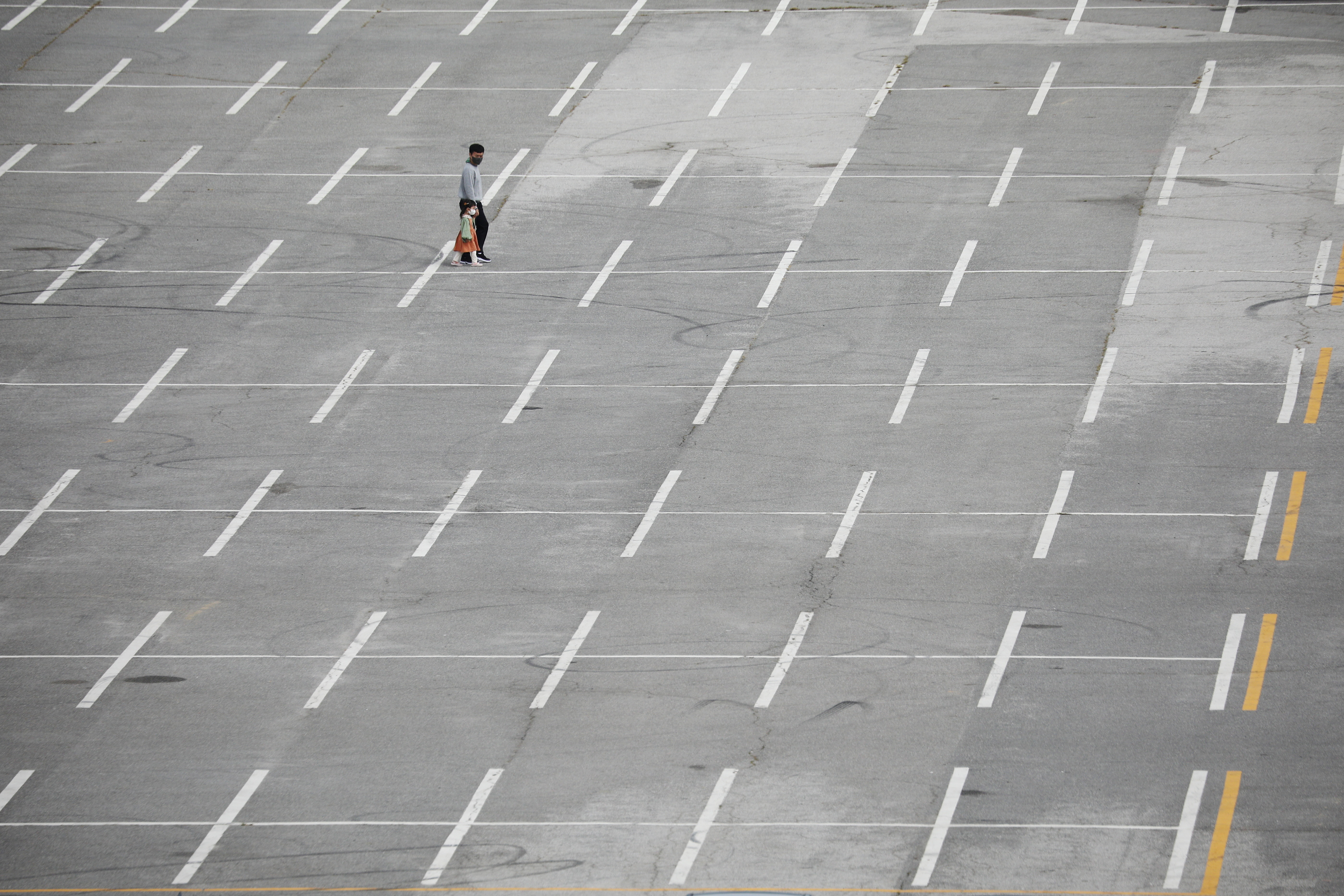 A father and his daughter wear masks to avoid contracting the coronavirus disease (COVID-19) as they walk on an empty parking lot of a park in Paju, South Korea, September 28, 2021. REUTERS/Kim Hong-Ji - RC2RYP92GJ2A