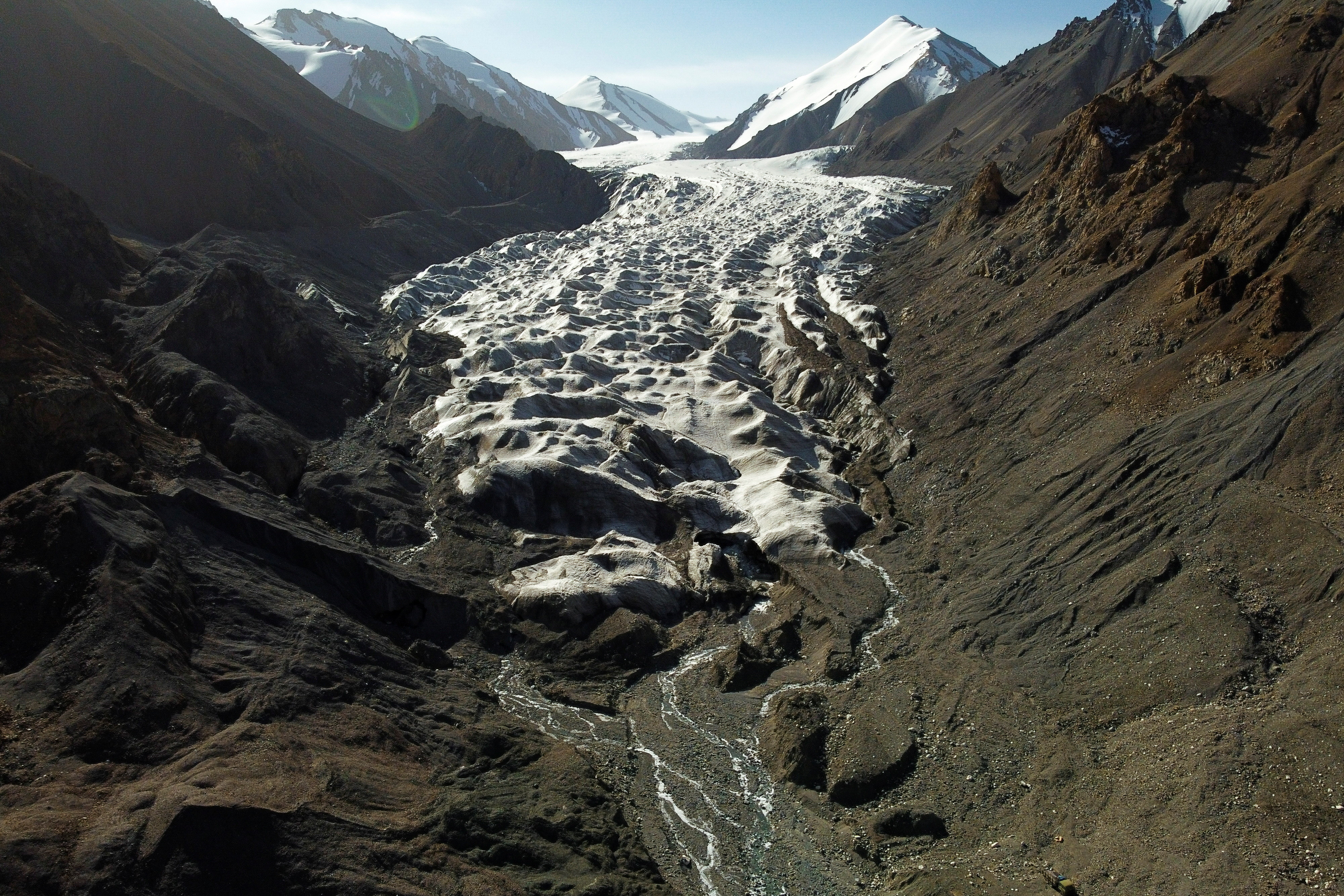 """Meltwater from the Laohugou No. 12 glacier, flows though the Qilian mountains, Subei Mongol Autonomous County in Gansu province, China, September 27, 2020. Glaciers in China's bleak, rugged Qilian mountains are disappearing at a shocking rate as global warming brings unpredictable change and raises the prospect of crippling, long-term water shortages, scientists say. The largest glacier in the 800-km (500-mile) mountain chain on the arid northeastern edge of the Tibetan plateau has retreated about 450 metres since the 1950s, when researchers set up China's first monitoring station to study it. Picture taken with a drone. REUTERS/Carlos Garcia Rawlins     SEARCH """"RAWLINS GLACIER"""" FOR THIS STORY. SEARCH """"WIDER IMAGE"""" FOR ALL STORIES. - RC2ZZJ9REZ5E"""