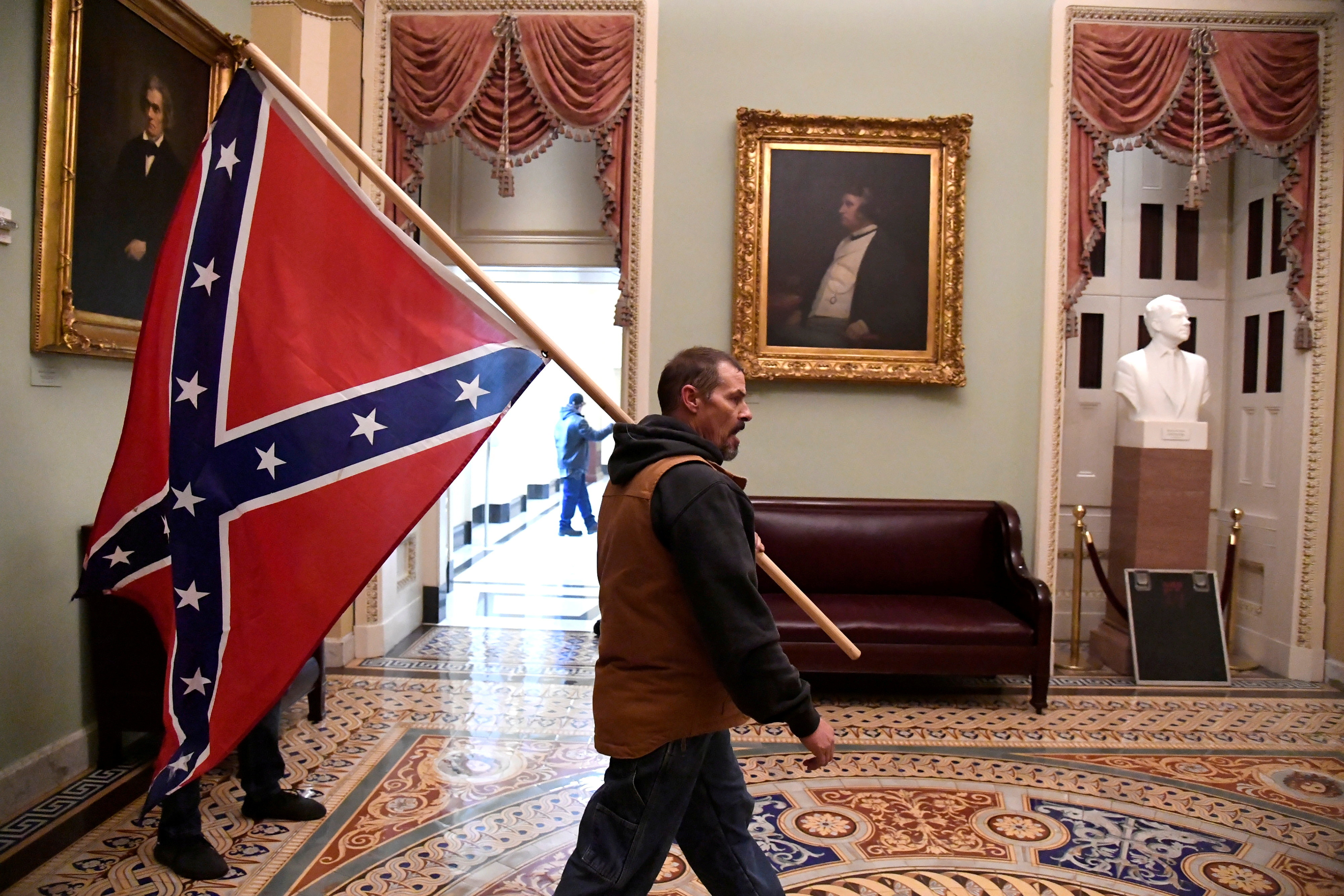 A supporter of President Donald Trump carries a Confederate battle flag on the second floor of the U.S. Capitol near the entrance to the Senate after breaching security defenses, in Washington, U.S., January 6, 2021. A portrait of abolitionist senator Charles Sumner of Massachusetts, who was savagely beaten on the Senate floor after delivering a speech criticizing slavery in 1856, hangs above the couch.        REUTERS/Mike Theiler     TPX IMAGES OF THE DAY - RC2K2L9T6BWB