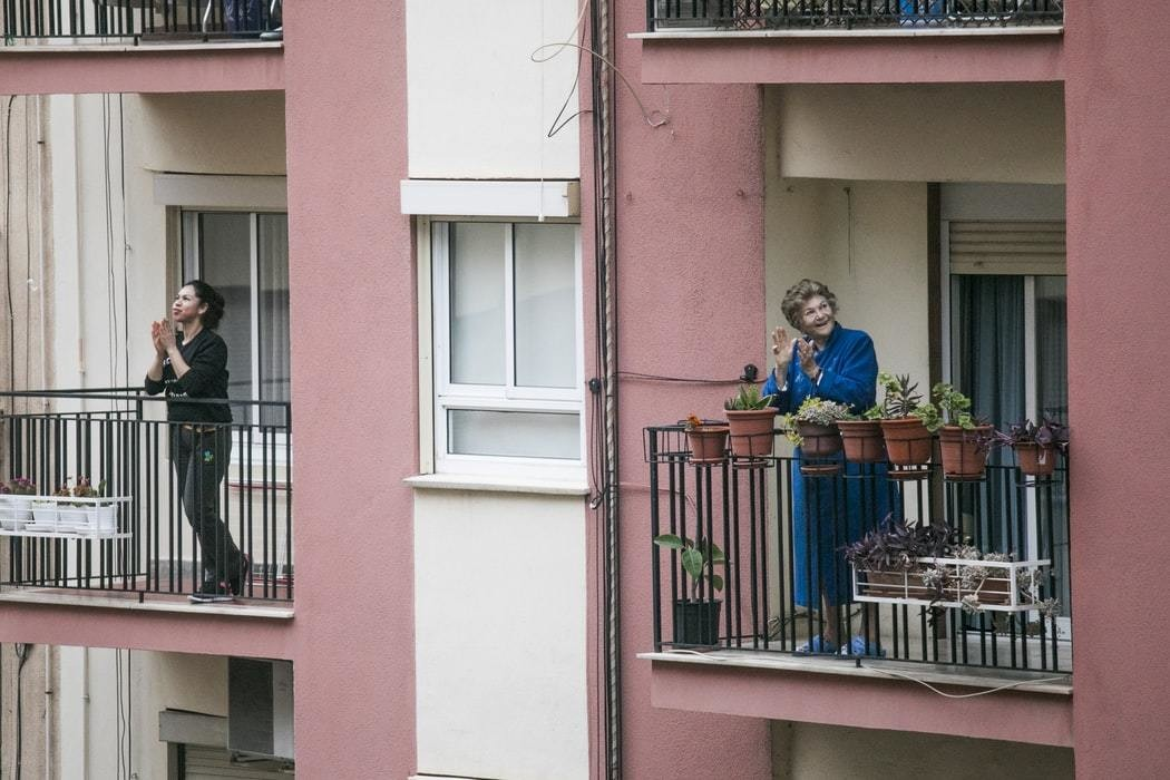 People stand on their balconies as Latin America introduces lockdown measures.