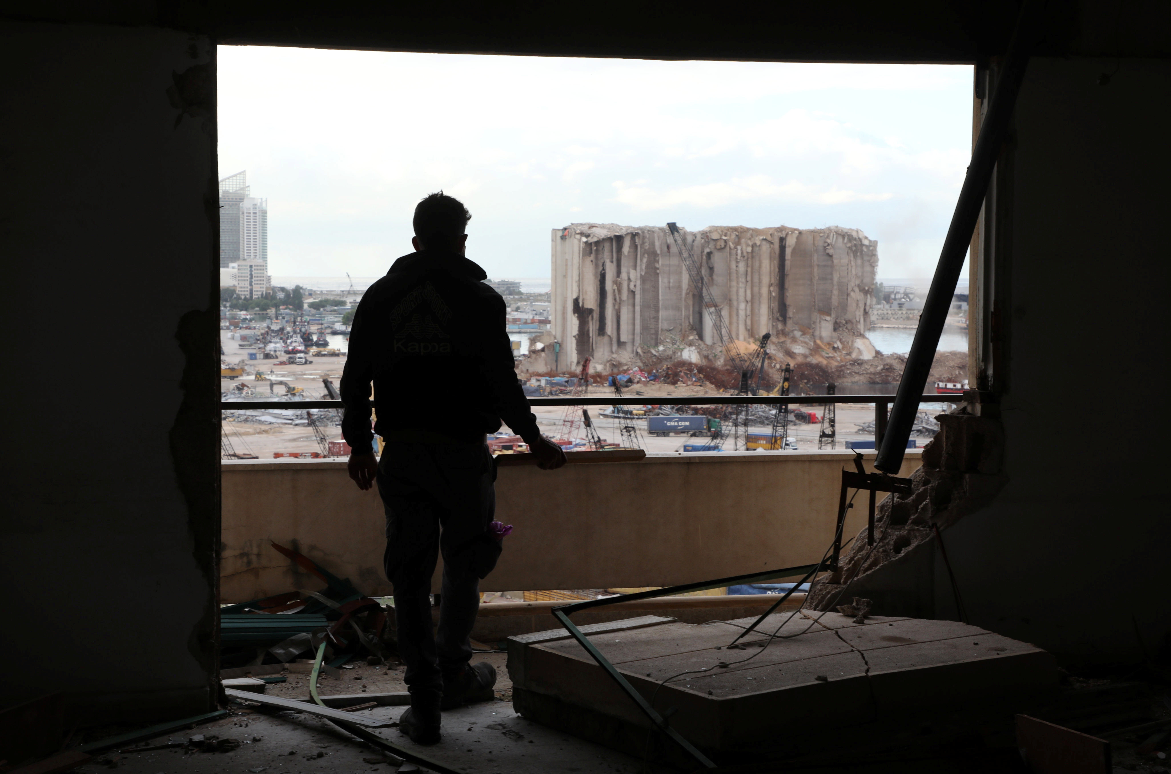 A worker inside a damaged building overlooking the site of the explosion at Beirut's port.