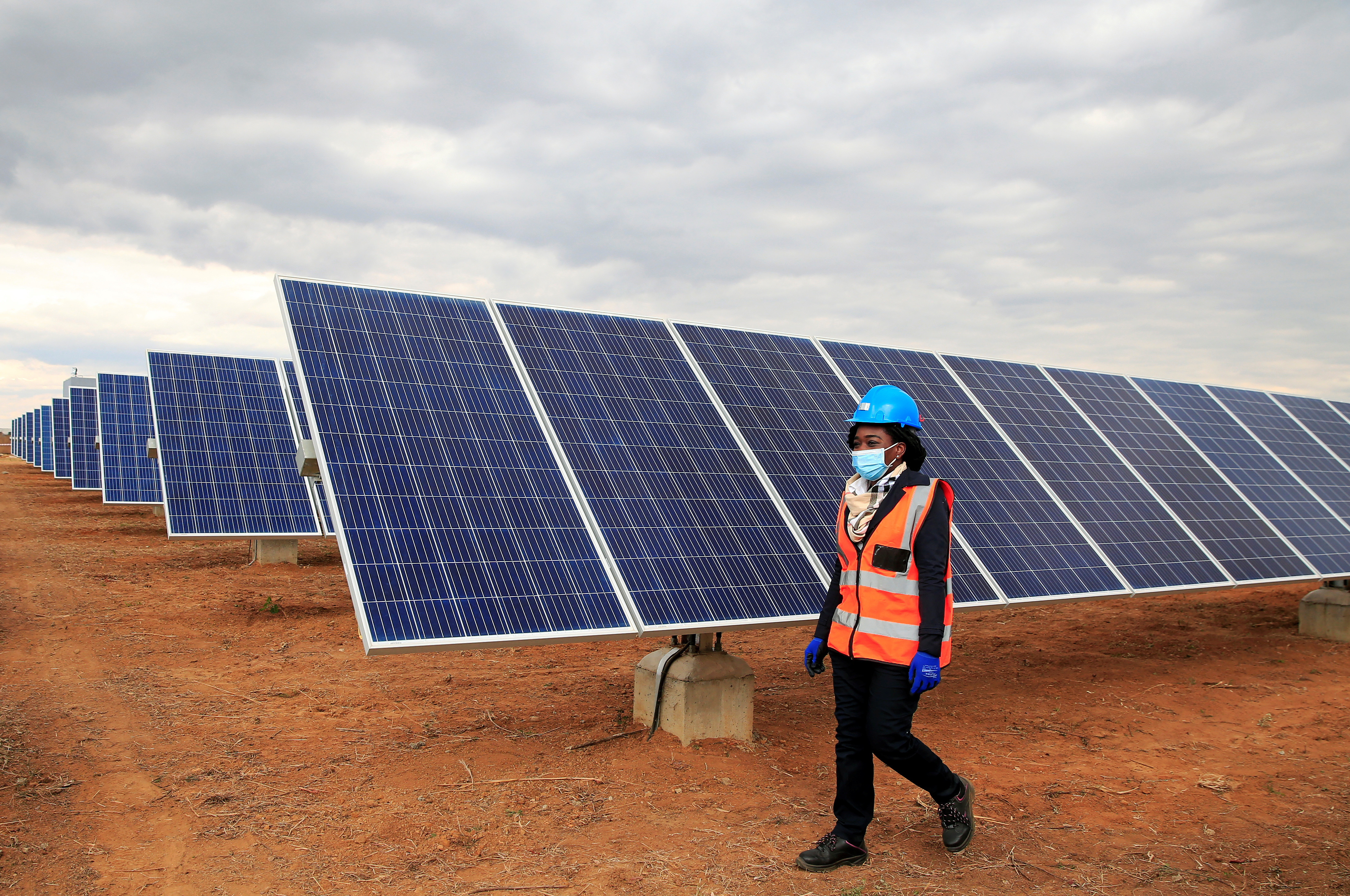 A worker walks past solar panels at Centragrid power plant in Nyabira, Zimbabwe, June 22, 2020. Picture taken June 22, 2020. REUTERS/Philimon Bulawayo - RC2XEH9KFHI5