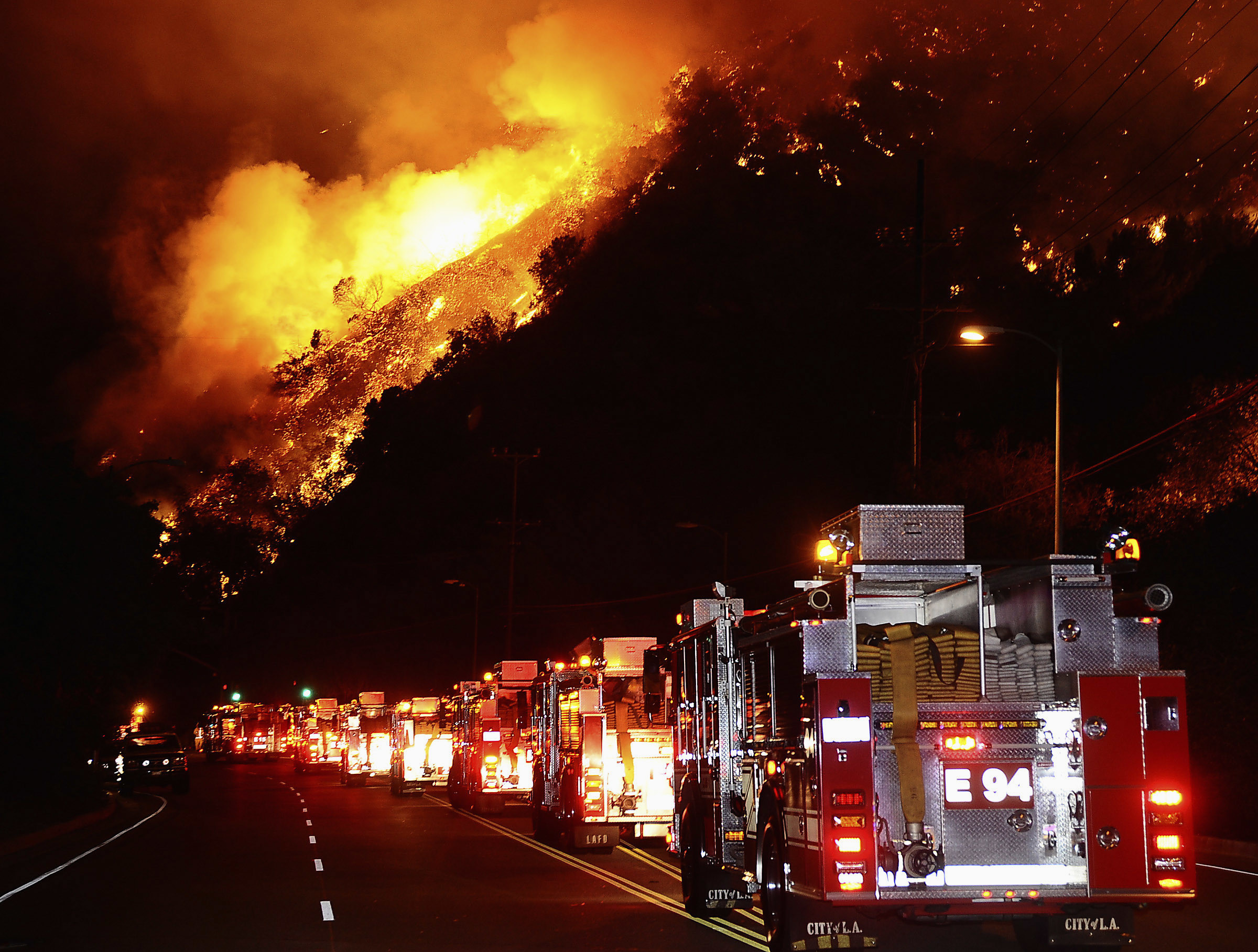 Fire trucks are shown lined up as a hillside burns during a brush fire in the Sepulveda Pass on the western edge of Los Angeles in the early morning of October 23, 2008. One hundred acres burned, threatening homes, but the blaze was extinguished without loss or injury.   REUTERS/Gene Blevins    (UNITED STATES) - GM1E4AO05TK01