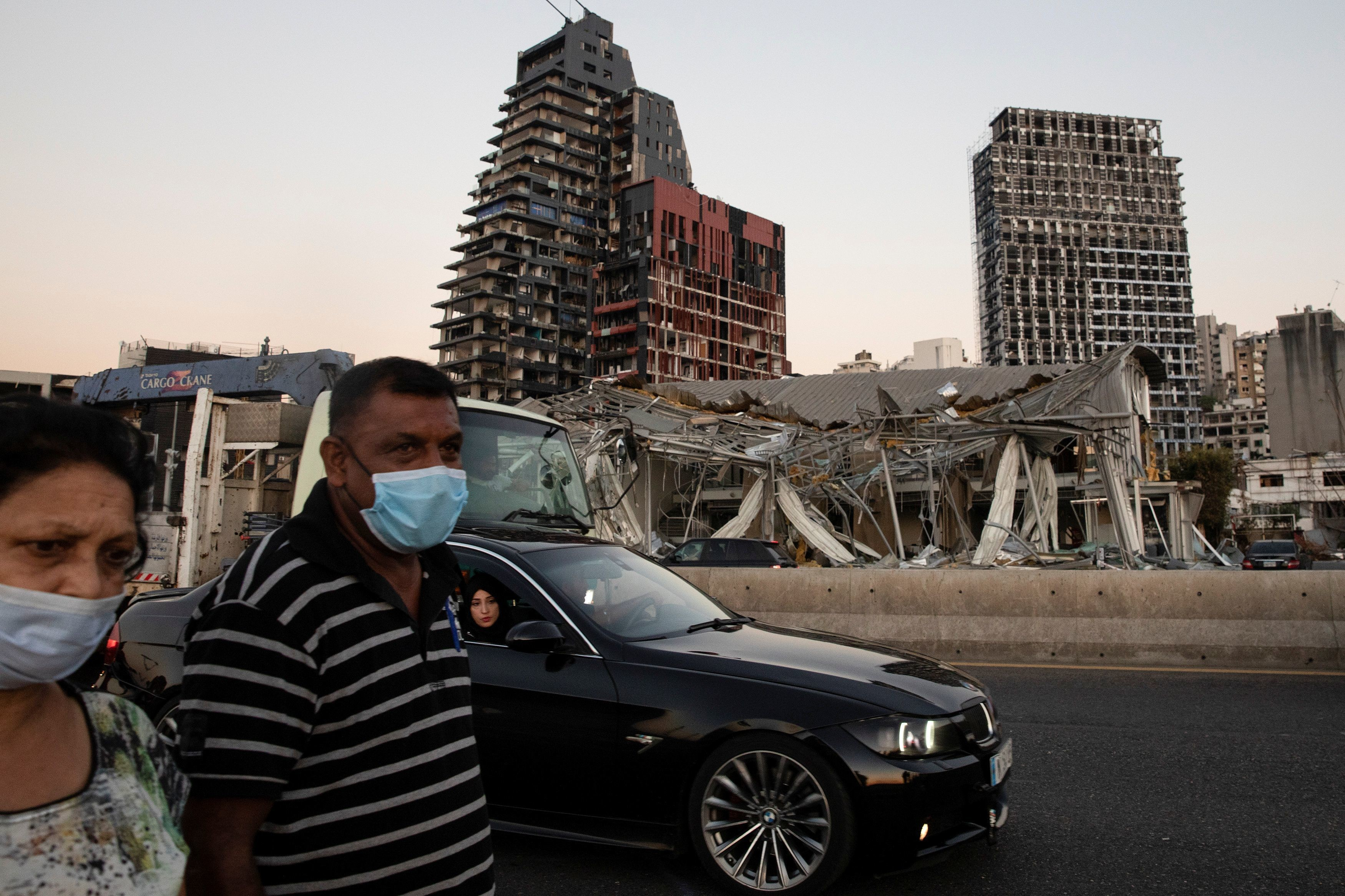 People pass by damaged buildings next to the port area, in the aftermath of a massive explosion, in Beirut, Lebanon, August 16, 2020. REUTERS/Alkis Konstantinidis - RC26FI9BKACH