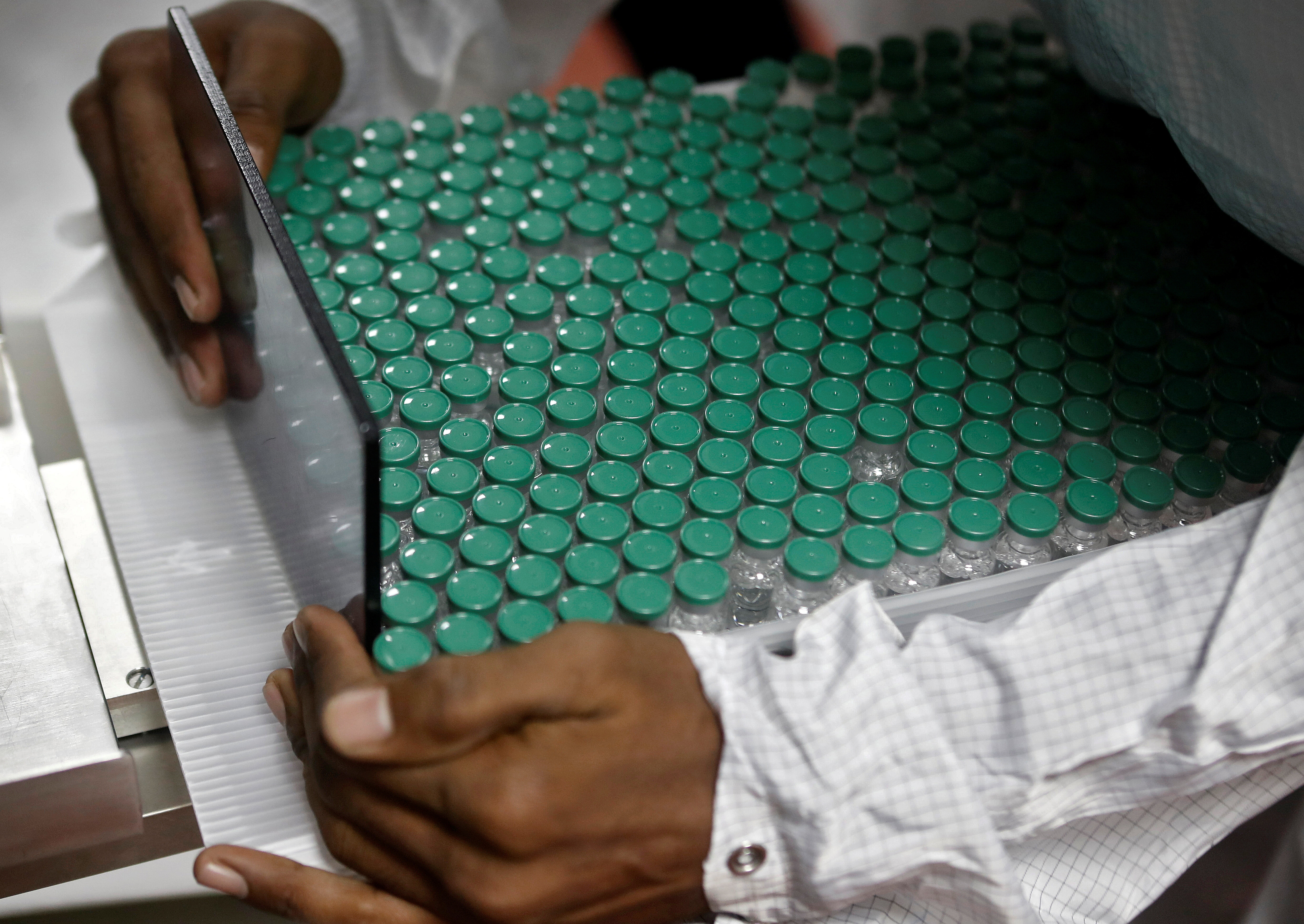 An employee in personal protective equipment (PPE) removes vials of AstraZeneca's COVISHIELD, coronavirus disease (COVID-19) vaccine from a visual inspection machine inside a lab at Serum Institute of India, in Pune, India, November 30, 2020. Picture taken November 30, 2020. REUTERS/Francis Mascarenhas - RC28EK9M111J