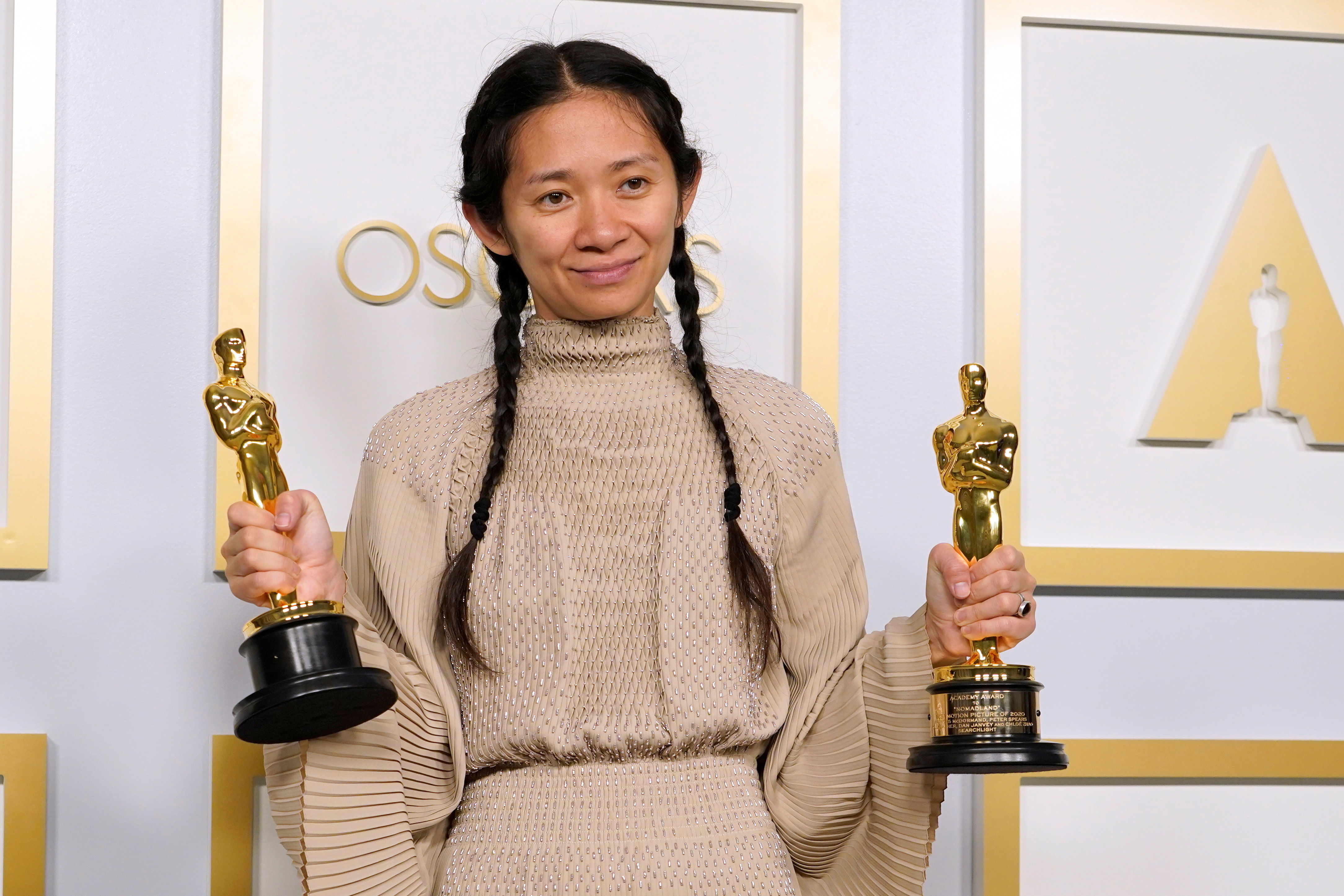 """photo of Chloe Zhao, winner of the award for Best Picture for """"Nomadland"""", holding her awards"""
