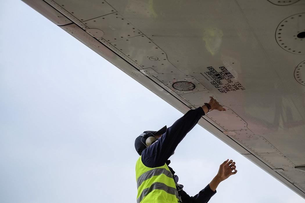An engineer refuelling a plane.