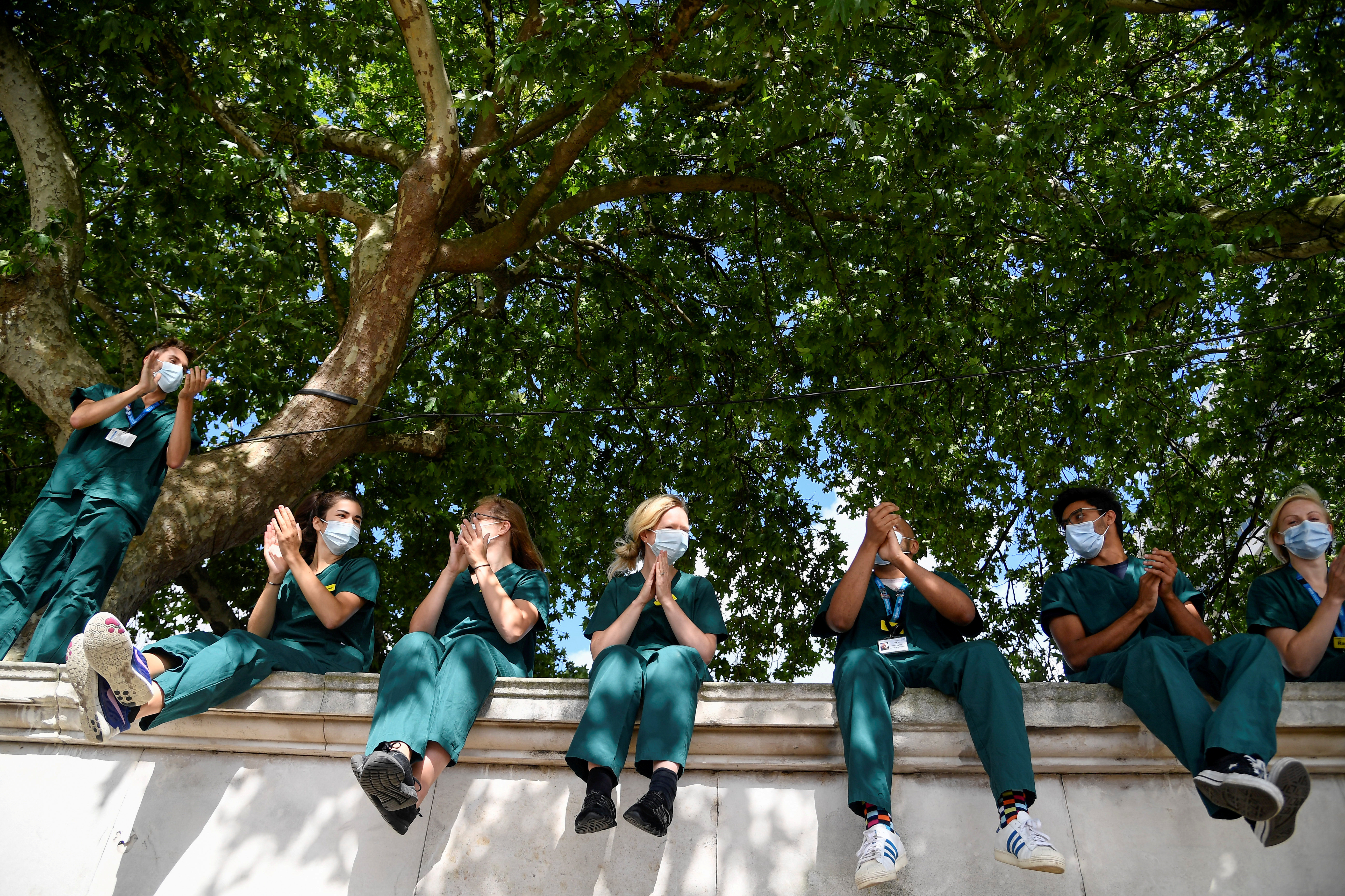 Health workers applaud outside St Thomas' Hospital on the occasion of the 72nd anniversary of the NHS, amid the coronavirus disease (COVID-19) outbreak, in London, Britain, July 5, 2020. REUTERS/Toby Melville     TPX IMAGES OF THE DAY - RC24NH929N5D