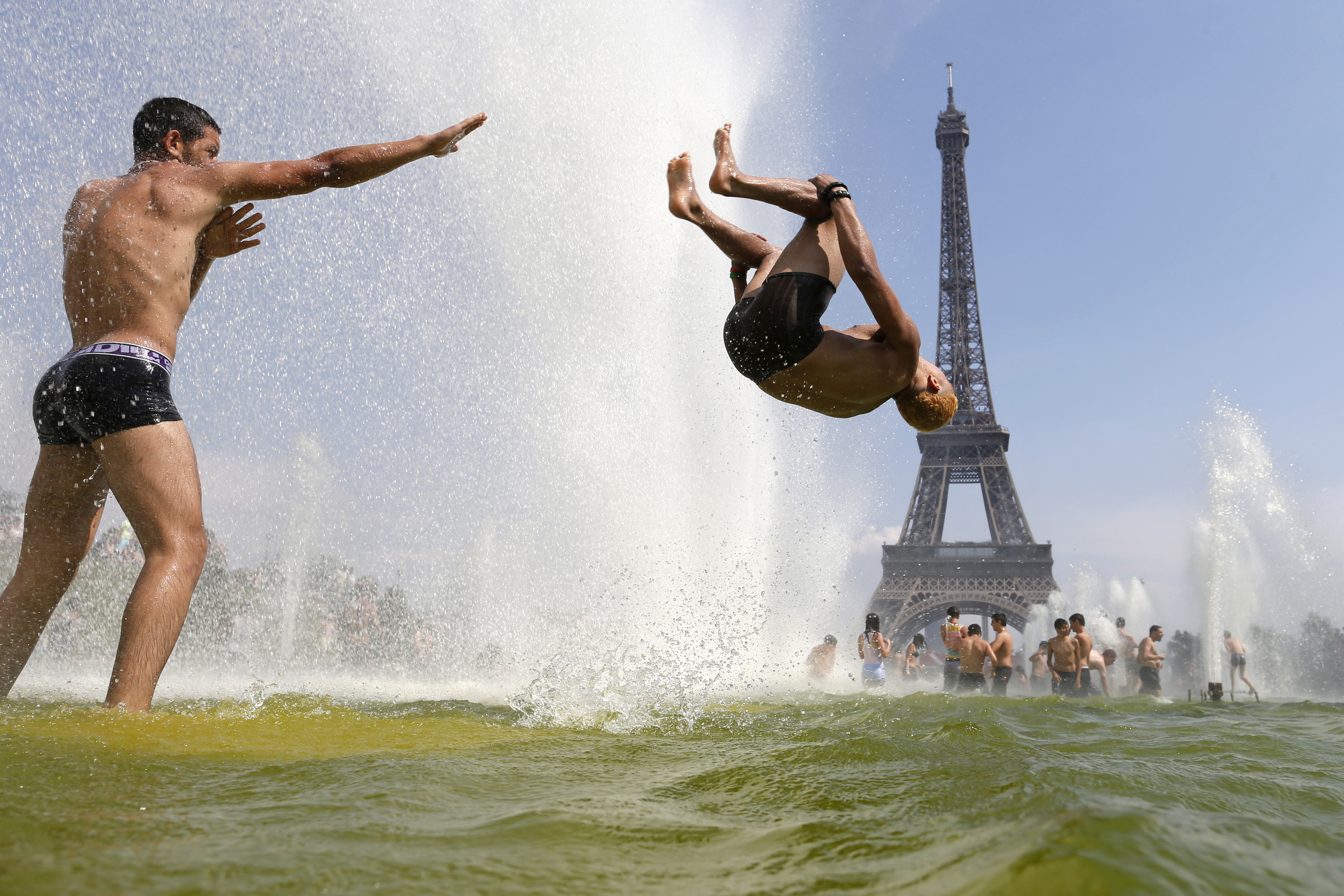 A man jumps in a fountain of the Trocadero Square in front of the Eiffel Tower as hot summer temperatures continue in Paris July 22, 2013.   REUTERS/Benoit Tessier  (FRANCE - Tags: TRAVEL ENVIRONMENT SOCIETY) - PM1E97M1AI601