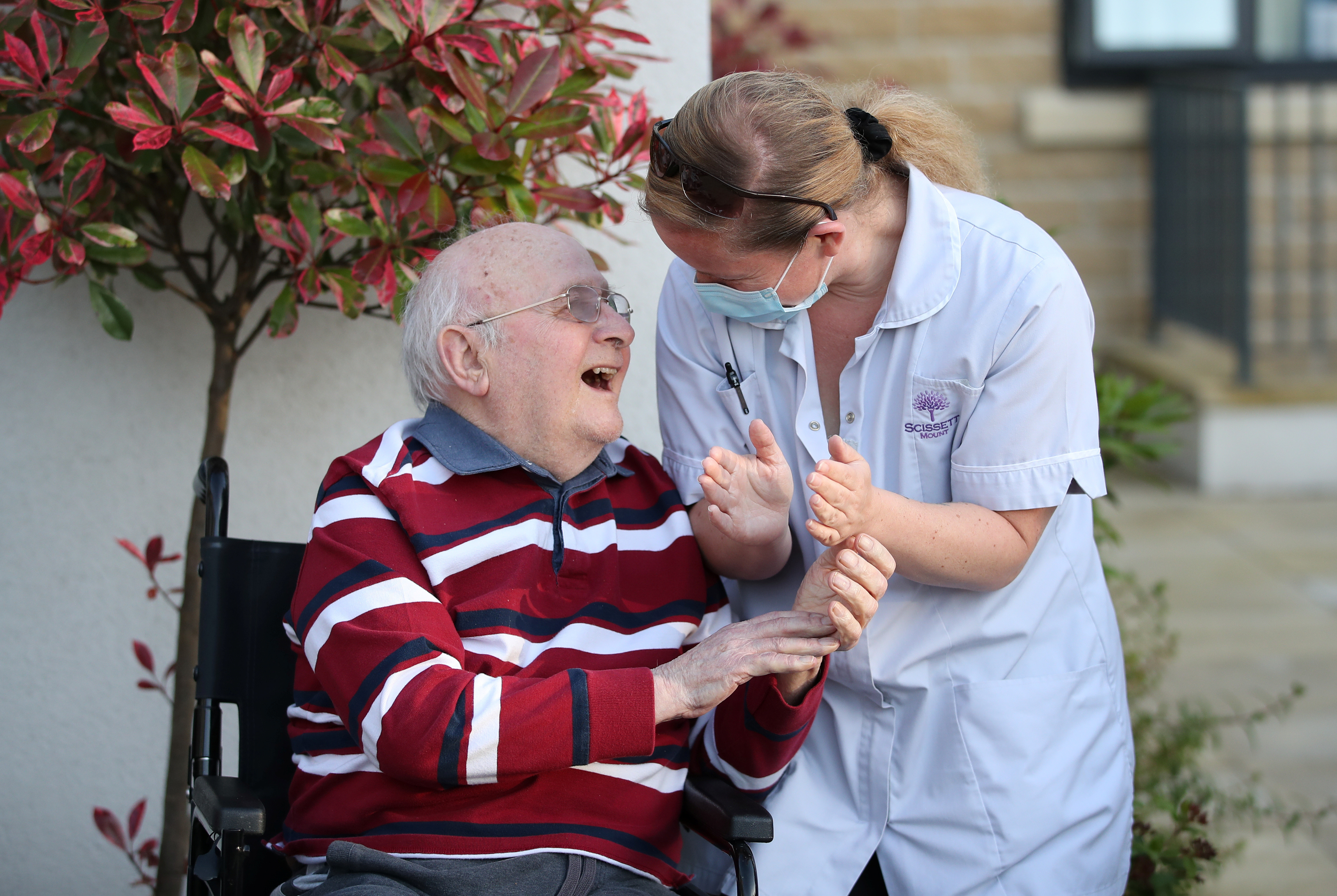 A Care worker and resident of the Scisset Mount Care Home react during the last day of the Clap for our Carers campaign in support of the NHS, following the outbreak of the coronavirus disease (COVID-19), Huddersfield, Britain, May 28, 2020.