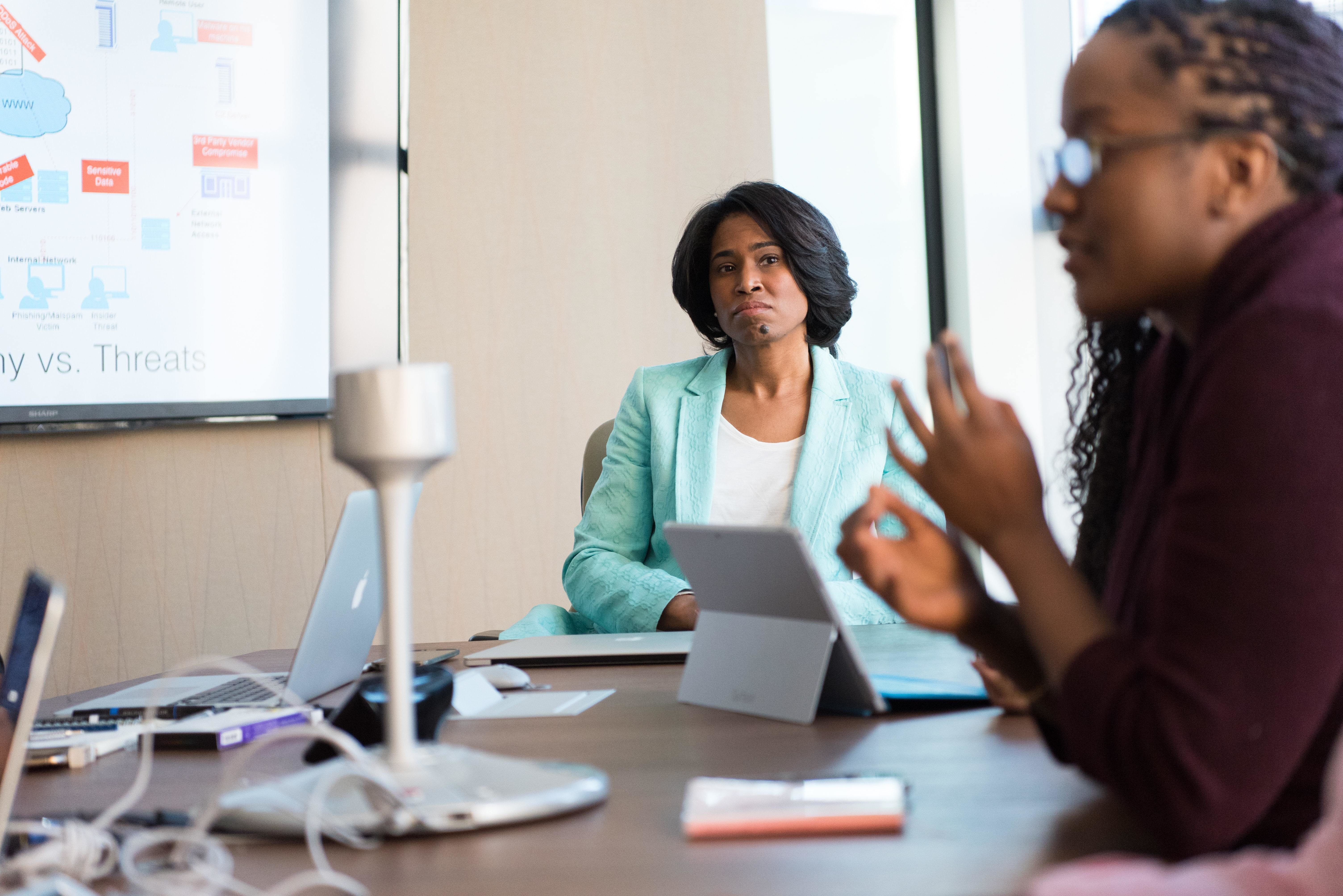 A business woman sits in a meeting room looking across to another employee
