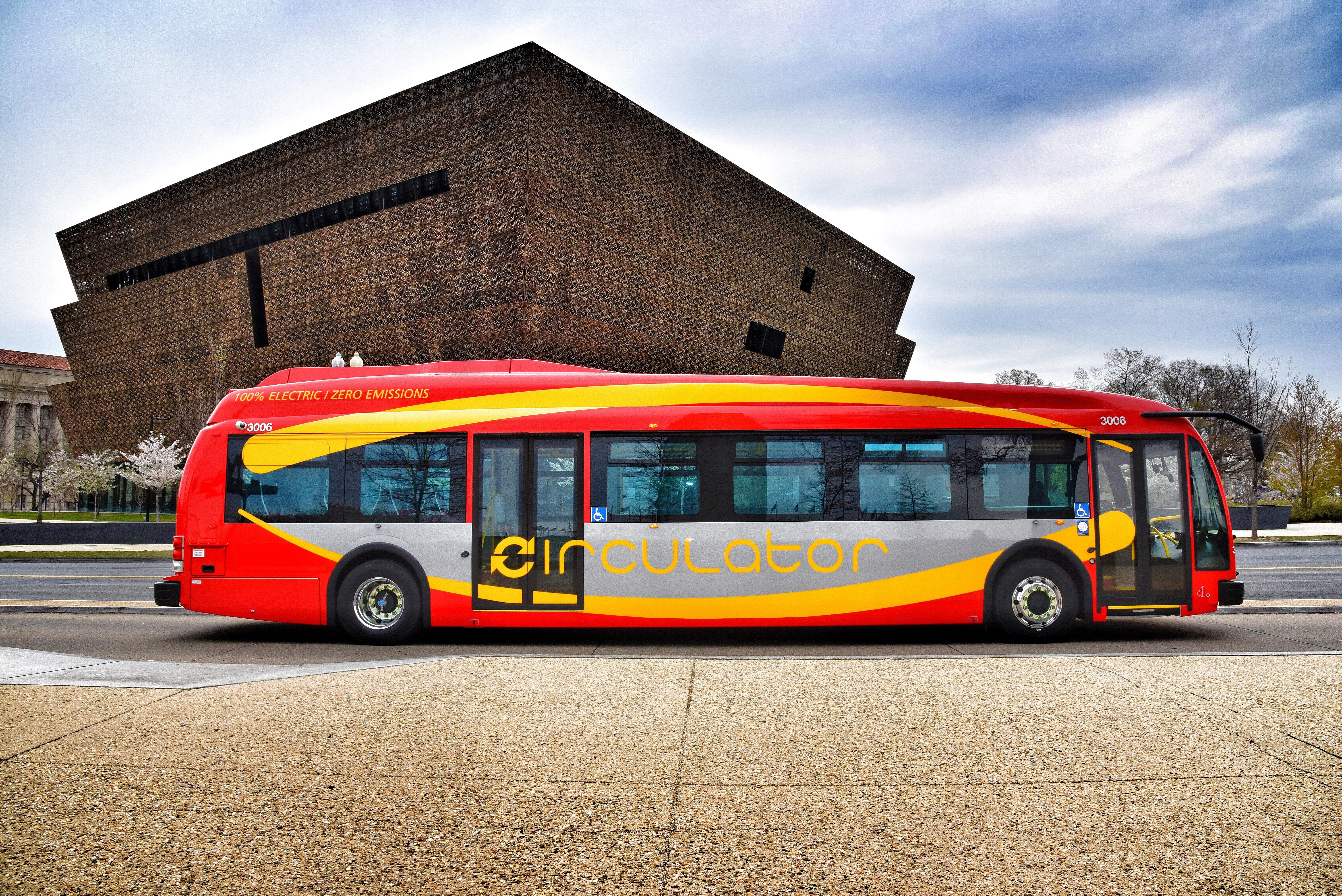 A red and yellow e-bus, the first used in Washington as passenger transport.