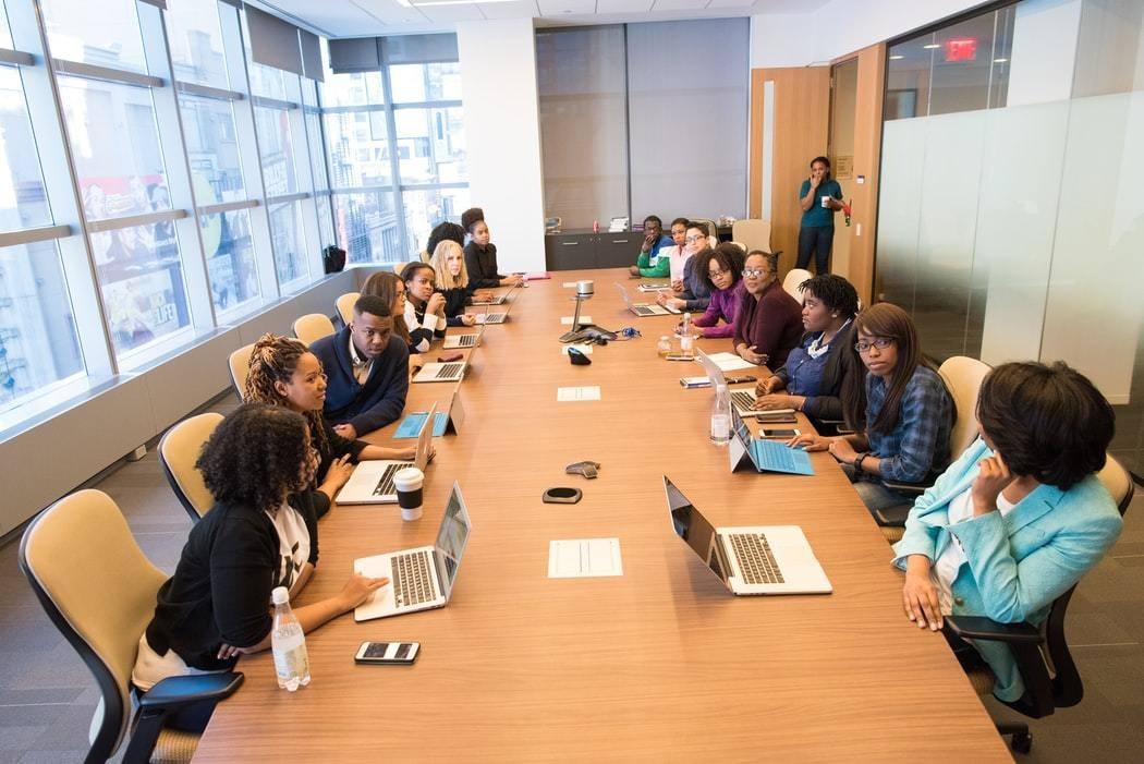 A boardroom filled with people of differing genders and races.