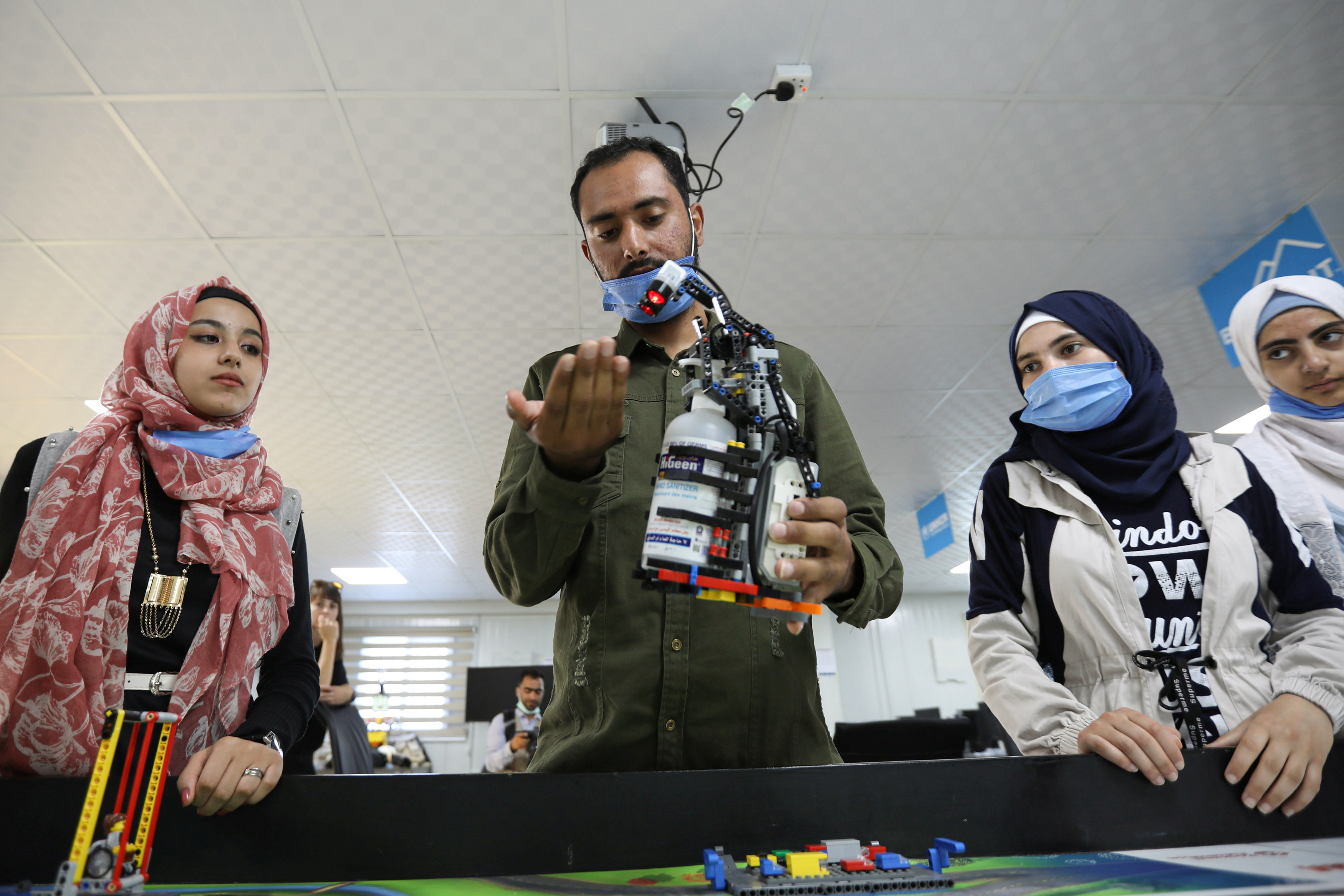 Syrian refugee students and instructor, Yasine Hariri, use his invention that is a robot prototype that automatically dispenses sanitiser to avoid contact and combat the spread of the coronavirus disease (COVID-19) as a part of the camp's UNHCR-led Innovation Lab program, at the Zaatari refugee camp in the Jordanian city of Mafraq, near the border with Syria, July 14, 2020. Picture taken July 14, 2020