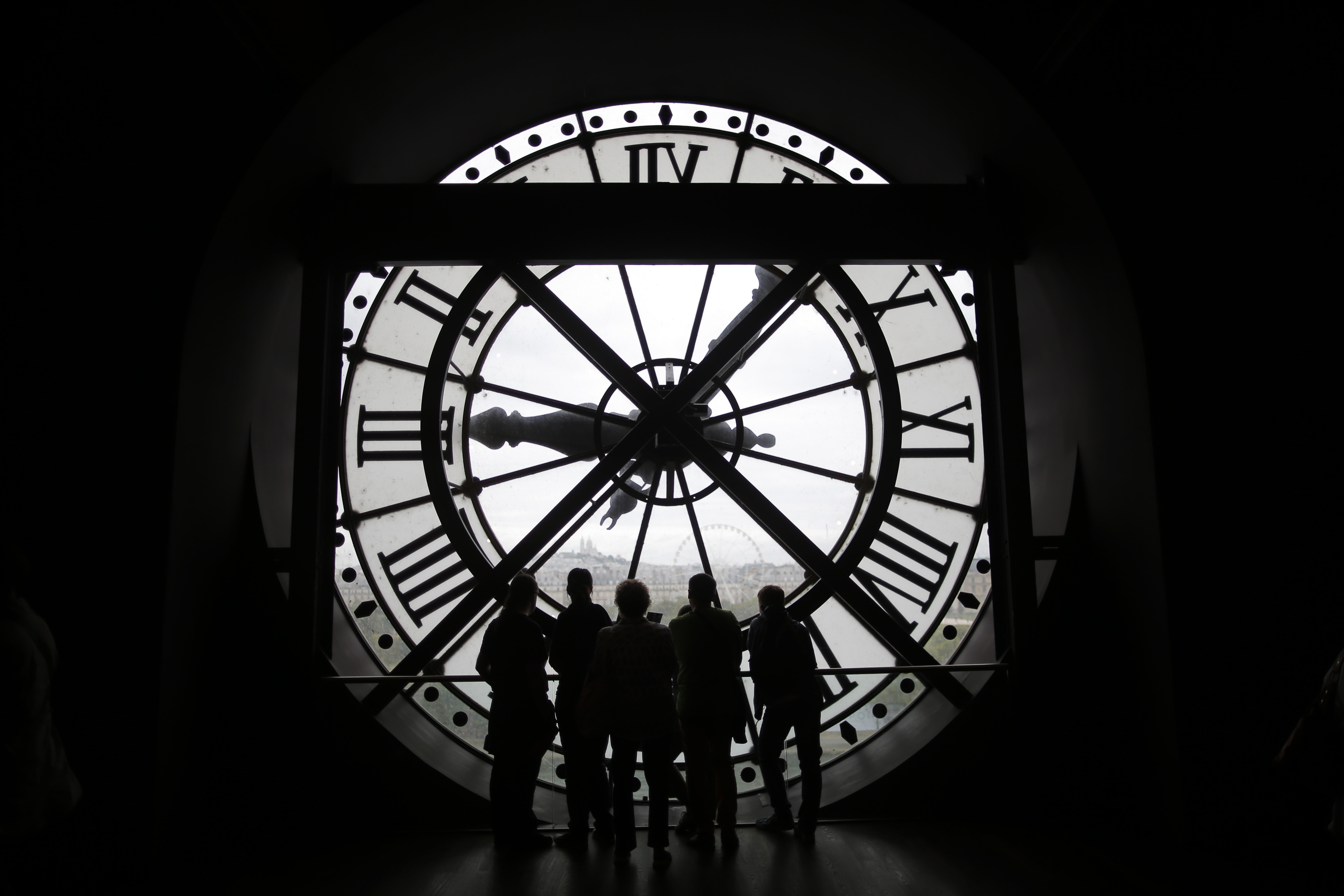 Visitors at the Musee d'Orsay are seen in silhouette as they look behind a giant clock face at the former Orsay railway station, in Paris, France July 28, 2015. The national museum of the Musee d'Orsay opened in December 1986 and it displays collections of art from the period 1848 to 1914.  France has been the world's most visited country since the 1980's, welcoming 84 million tourists last year.   REUTERS/Stephane Mahe - PM1EB7S1DSU01