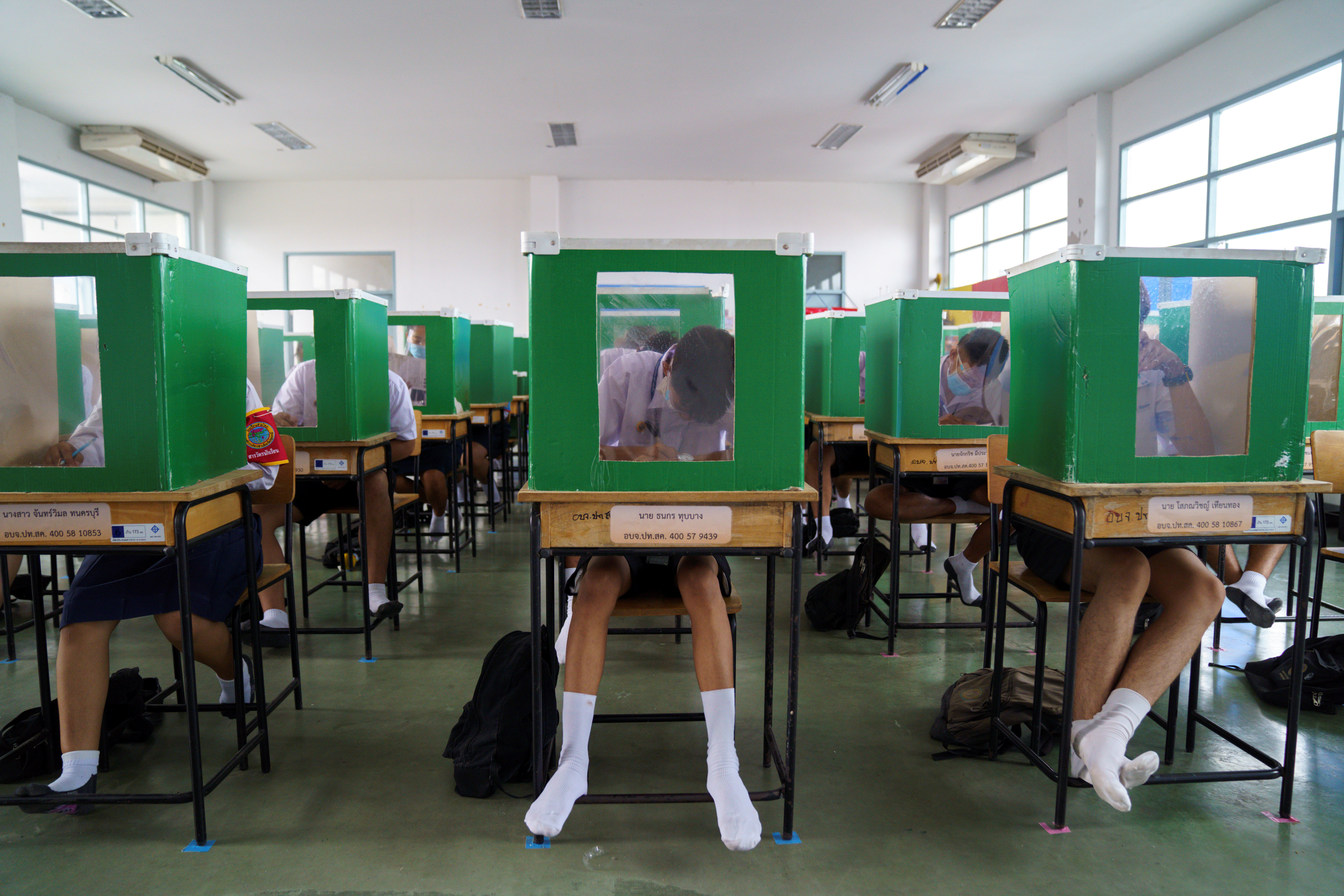 Students of Sam Khok school wearing face masks and face shields are seen inside old ballot boxes repurposed into partitions as they attend a class after the Thai government eased isolation measures and introduced social distancing to prevent the spread of the coronavirus disease (COVID-19), as schools nationwide reopen, at Pathum Thani province, Thailand, July 1, 2020. REUTERS/Athit Perawongmetha     TPX IMAGES OF THE DAY - RC24KH9TZD5O