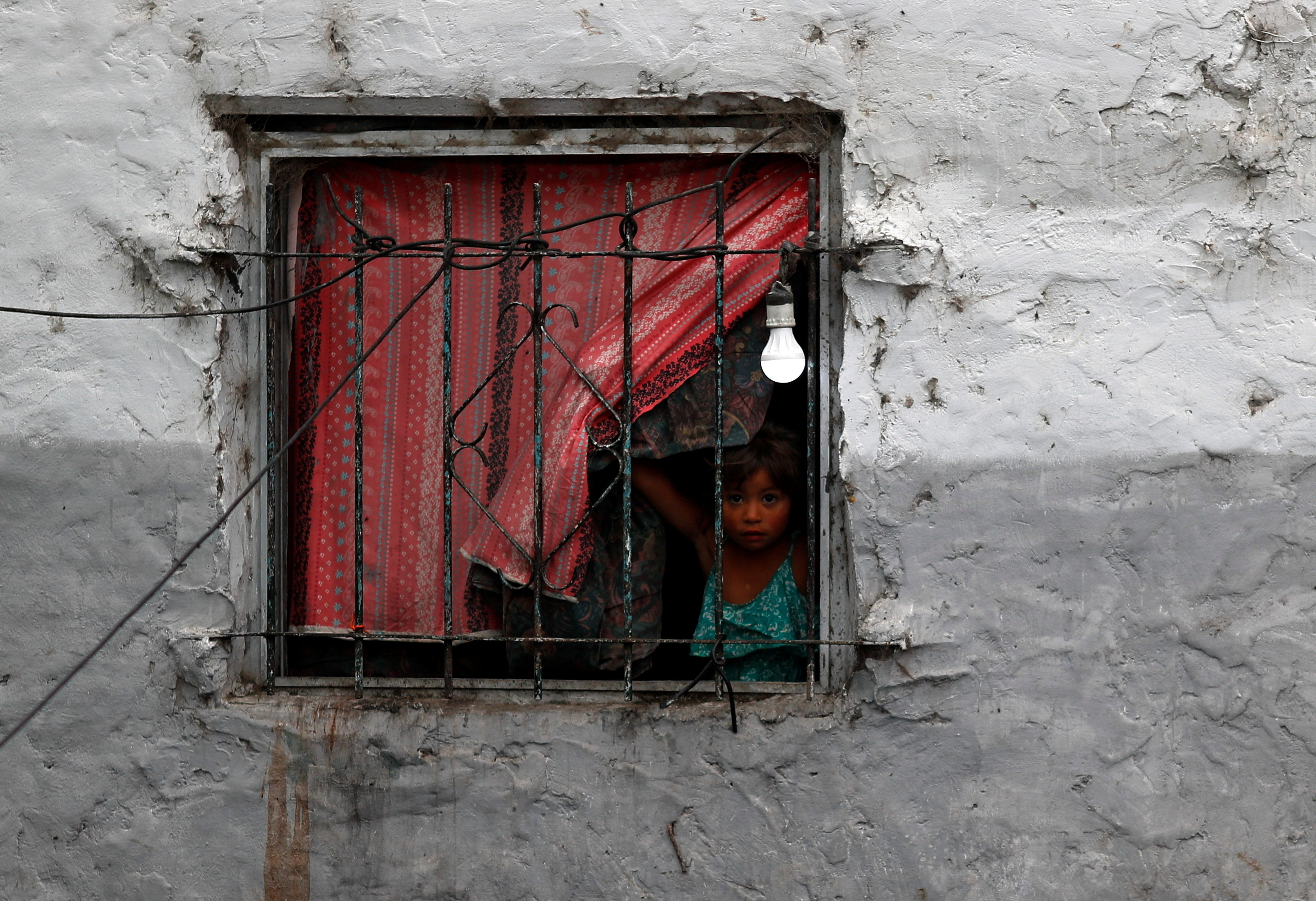 A girl looks from the window of her family's house, during the coronavirus disease (COVID-19) outbreak, in Buenos Aires, Argentina December 15, 2020. Picture taken December 15, 2020. REUTERS/Agustin Marcarian - RC22PK9MCBX2