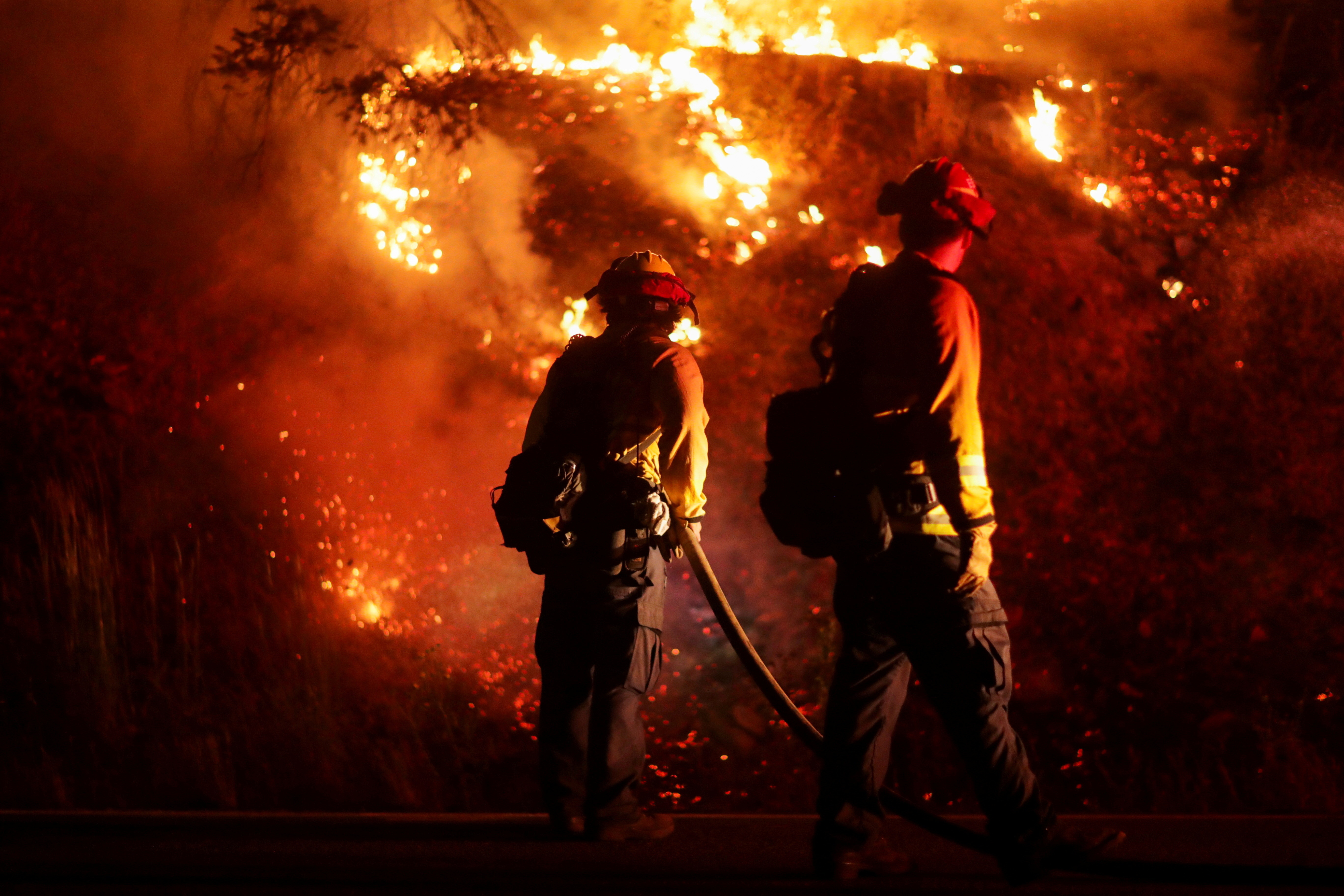 Firefighters extinguish spot fires along Route 89 Dixie Fire in Moccasin, now over 200,000 acres, California, U.S., July 28, 2021