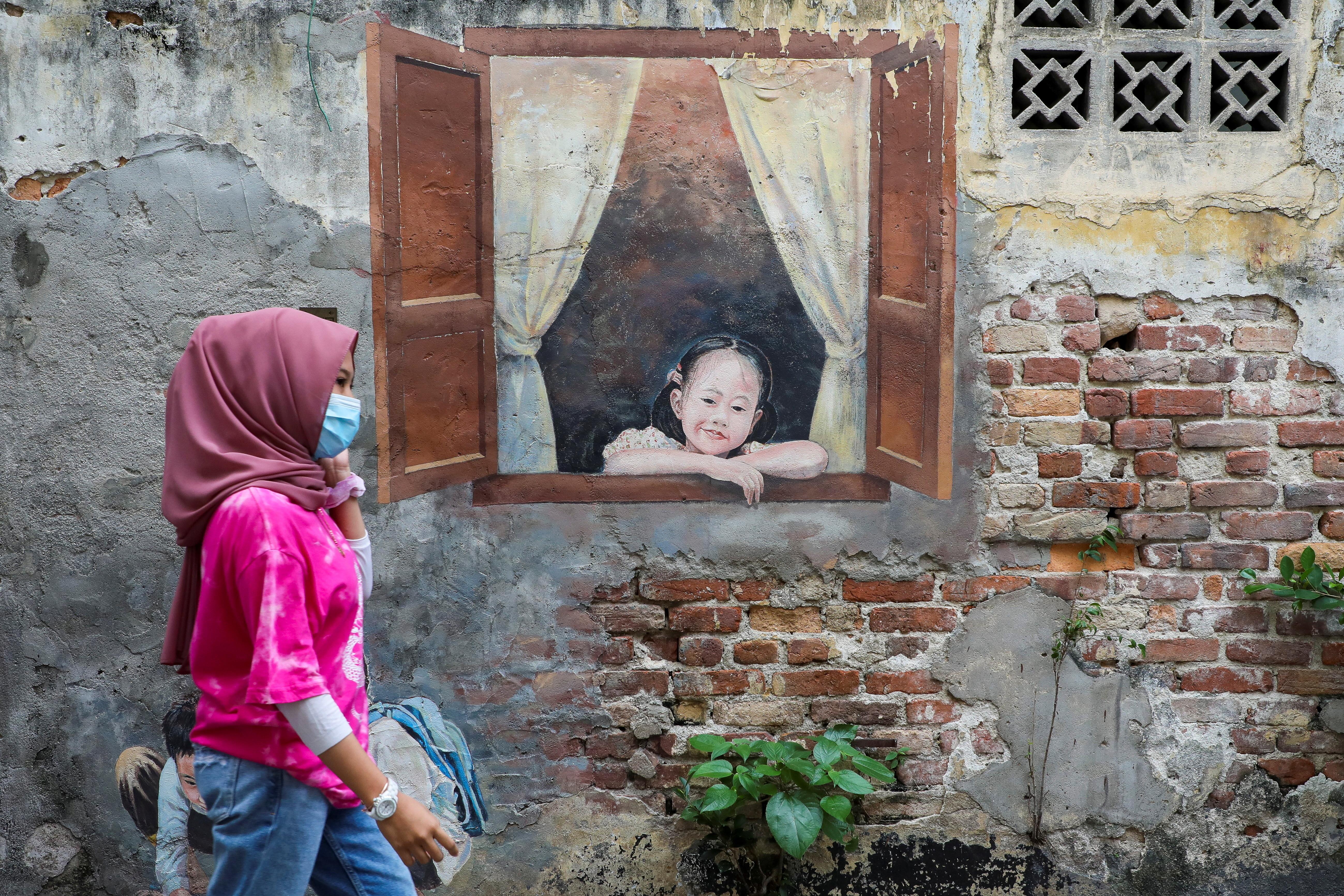 A woman wearing a protective mask walks past a mural, amid the coronavirus disease (COVID-19) outbreak in Kuala Lumpur, Malaysia January 12, 2021. REUTERS/Lim Huey Teng - RC2A6L97PLAR
