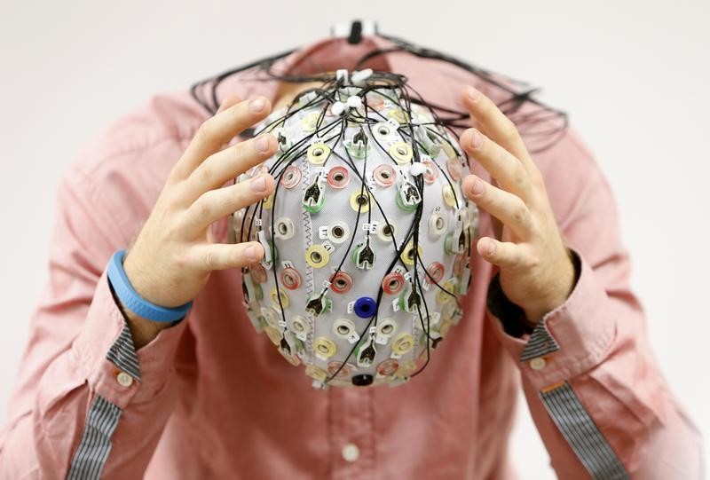 Test person Niklas Thiel poses with an electroencephalography (EEG) cap which measures brain activity, at the Technische Universitaet Muenchen (TUM) in Garching near Munich September 9, 2014. The researchers from TUM and the Technische Universitaet Berlin (team Phypa) try to find ways to control an airplane with computer translated brain impulses without the pilot touching the plane's controls. The solution, if achieved, would contribute to greater flight safety and reduce pilots' workload. Picture taken September 9, 2014.    REUTERS/Michaela Rehle (GERMANY - Tags: SCIENCE TECHNOLOGY SOCIETY TPX IMAGES OF THE DAY) - BM2EA9914OF01