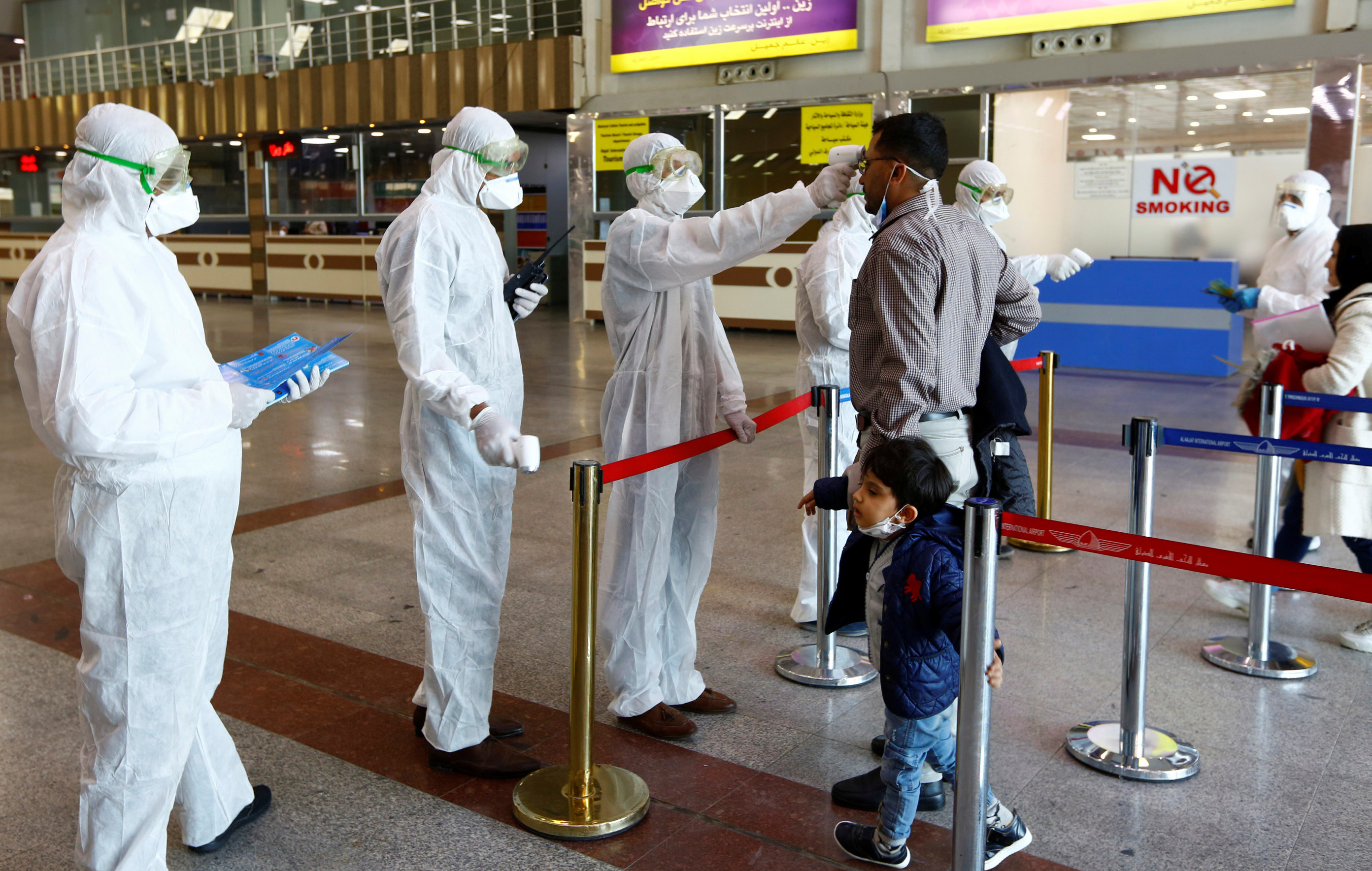 Iraqi medical staff check passengers' temperature, amid coronavirus outbreak, upon their arrival from Iran, at Najaf airport, Iraq March 5, 2020. REUTERS/Alaa al-Marjani - RC2QDF9IT3JA