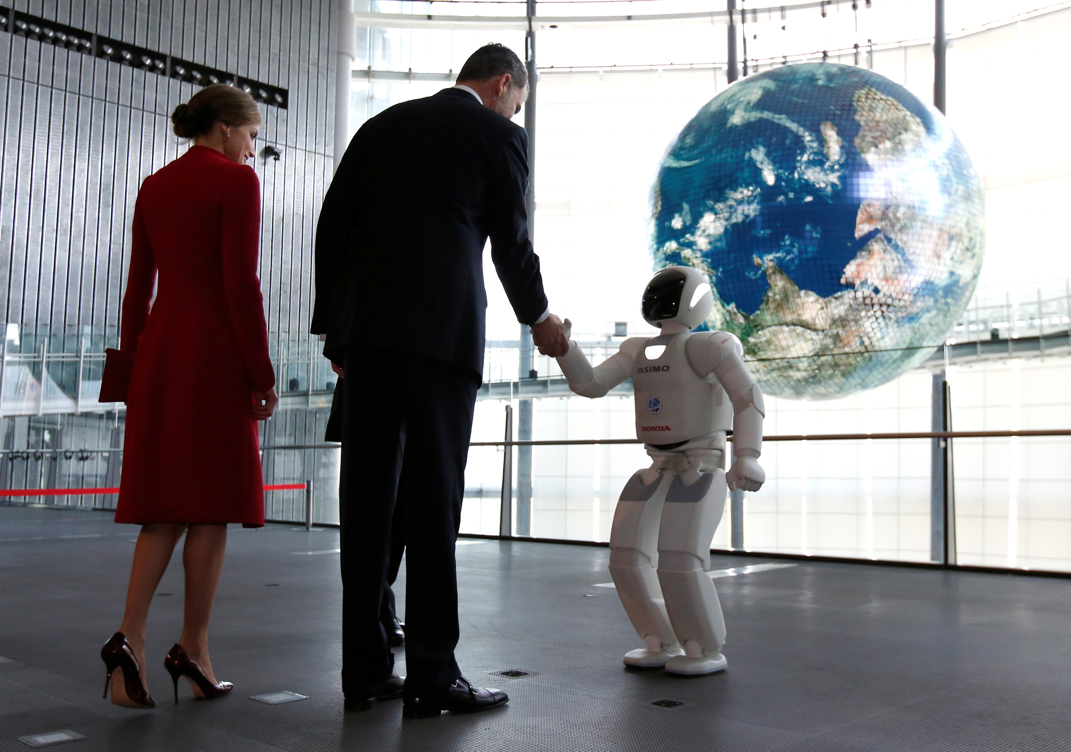 Spain's King Felipe, accompanied by Queen Letizia (L), shakes hands with Honda Motor's humanoid robot Asimo as they visit Miraikan (National Museum of Emerging Science and Innovation) in Tokyo, Japan April 5, 2017. REUTERS/Issei Kato     TPX IMAGES OF THE DAY - RC16A2135340