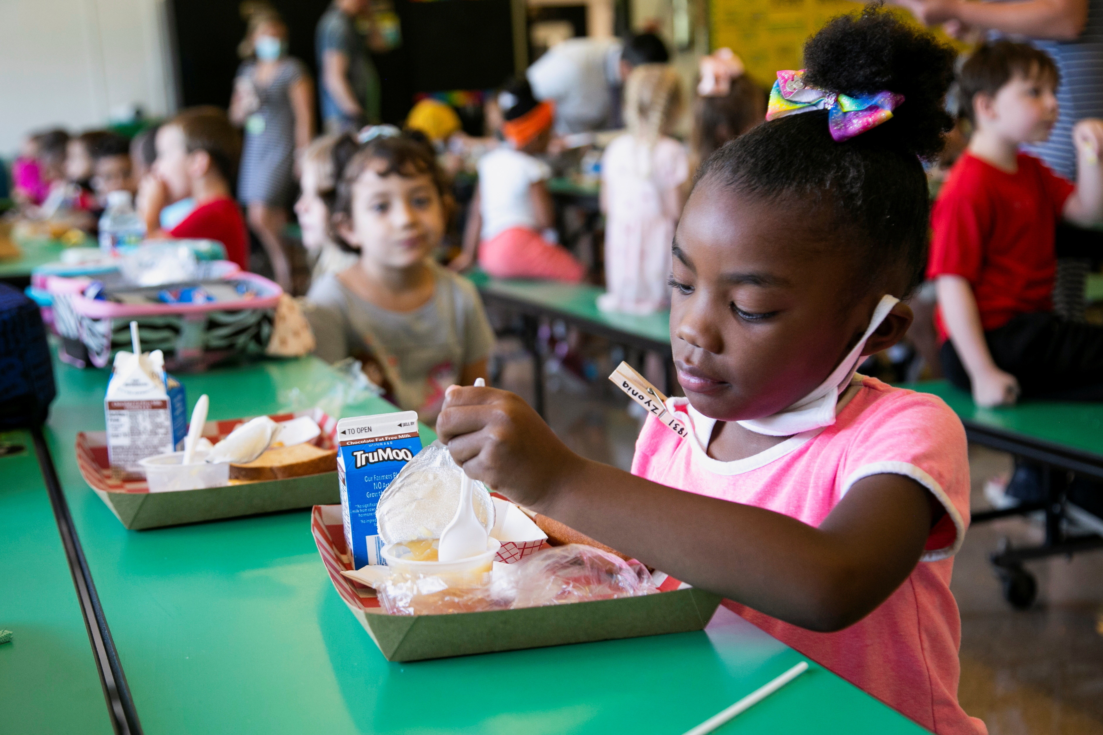 A student takes away her mask as she eats lunch at Wilder Elementary School in Louisville, KY, Kentucky.