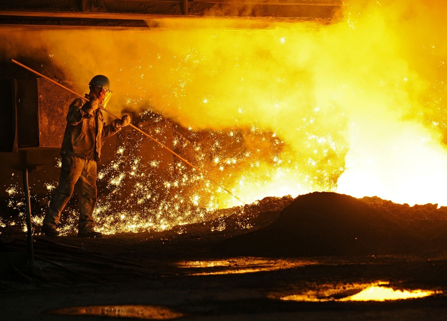 An employee works next to molten iron at a steel mill of Dongbei Special Steel in Dalian, Liaoning province, China July 17, 2018. REUTERS/Stringer  ATTENTION EDITORS - THIS IMAGE WAS PROVIDED BY A THIRD PARTY. CHINA OUT. - RC1EE6BD4C50