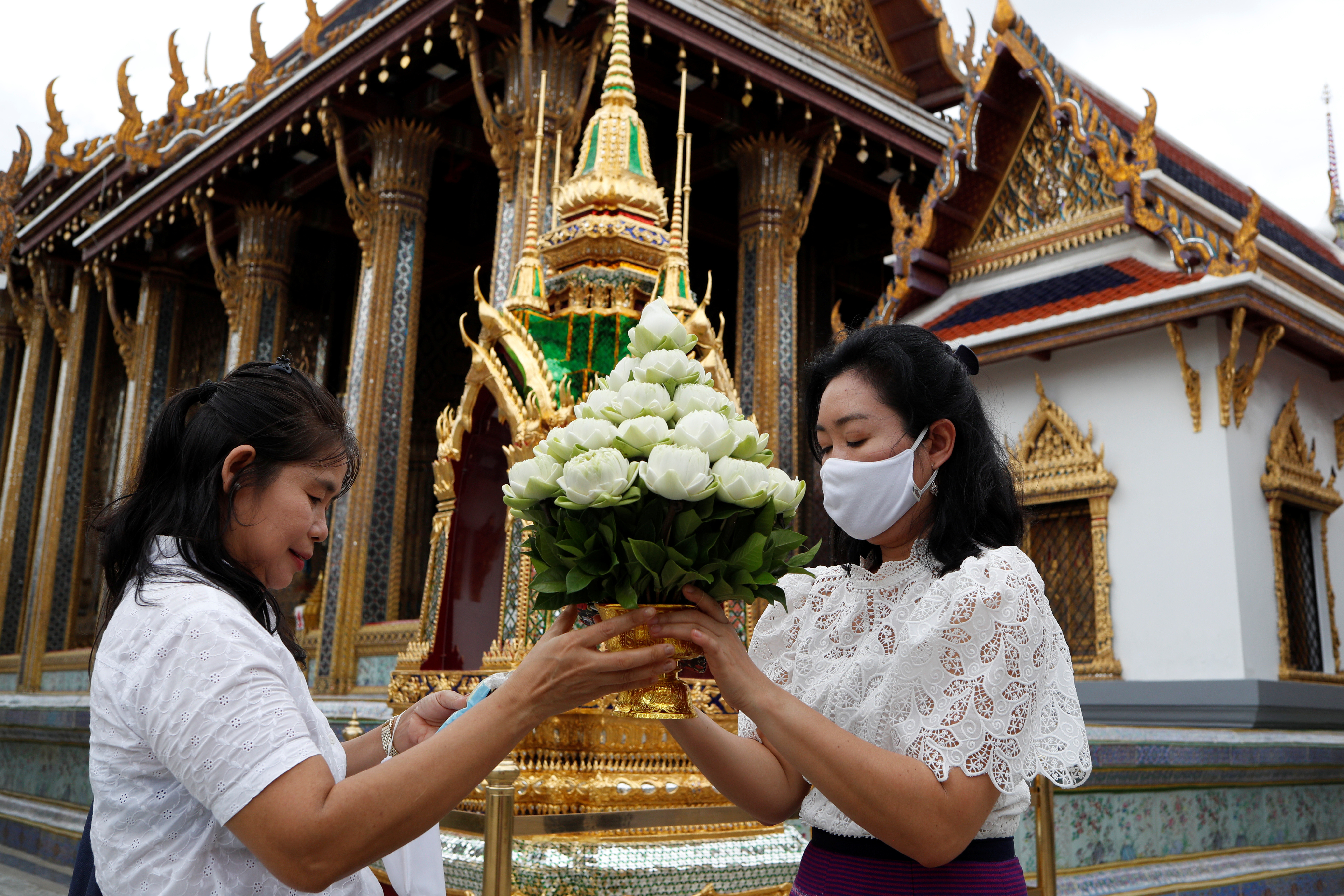 People visiting the Grand Palace hold flowers, as it reopens after months of being closed, as the Thai government eases isolation measures, amid the spread of the coronavirus disease (COVID-19) in Bangkok, Thailand, June 7, 2020. REUTERS/Jorge Silva - RC264H97PEHW