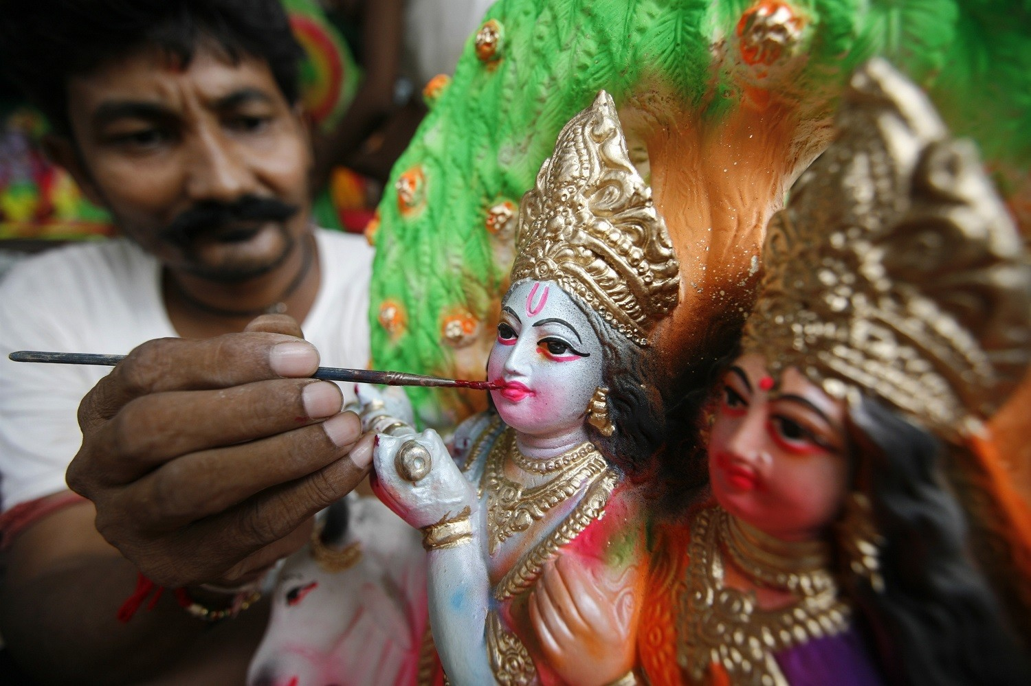 """An artisan paints an idol of the Hindu Lord Krishna ahead of """"Janamashtmi"""", at a roadside workshop in the western Indian city of Ahmedabad August 28, 2010. The idols will be displayed in temples on the occasion of """"Janamashtmi,"""" the birth anniversary of Lord Krishna on September 2. REUTERS/Amit Dave (INDIA - Tags: SOCIETY RELIGION) - GM1E68S1NLX01"""