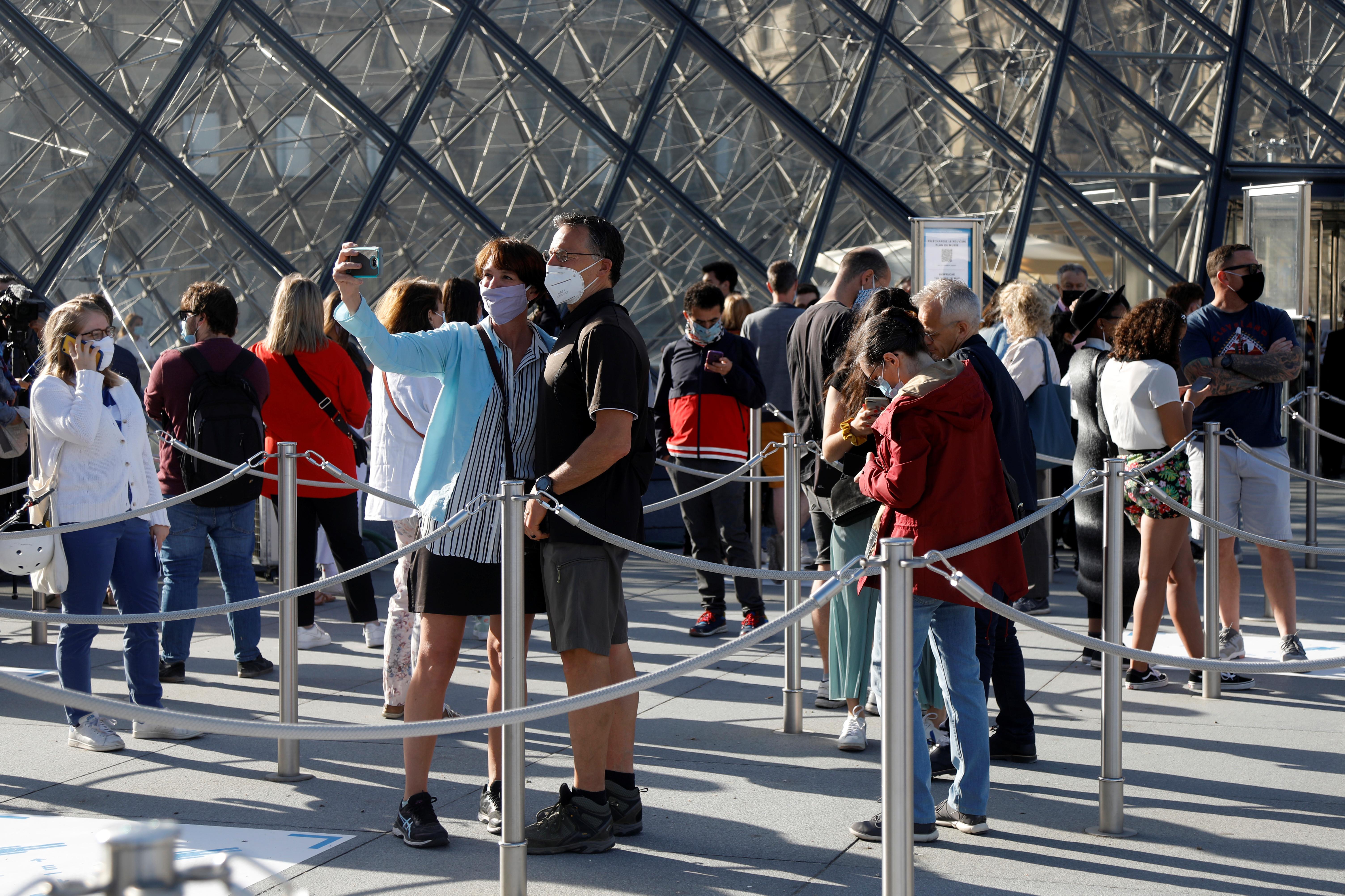 Los visitantes hacen cola frente a la Pirámide del Louvre diseñada por el arquitecto estadounidense nacido en China Ieoh Ming Pei en París mientras el museo reabre sus puertas al público después de casi 4 meses de cierre debido al brote de la enfermedad coronavirus (COVID-19) en Francia, el 6 de julio de 2020.