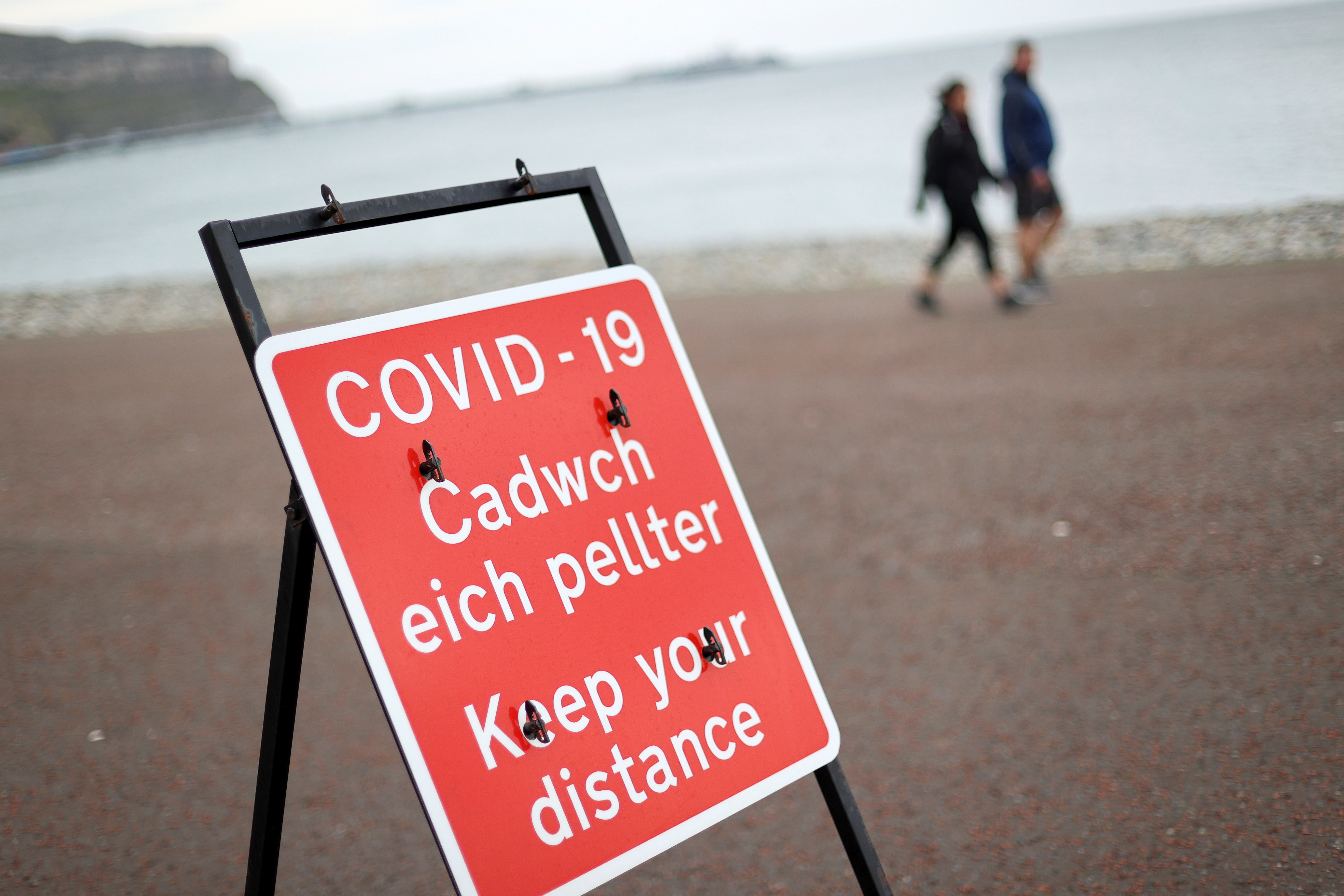 A social distancing sign is seen as people walk in the background, as the Welsh Government is set to impose stricter lockdown measures to try to curb the spread of the coronavirus disease (COVID-19), in Llandudno, Britain October 19, 2020. REUTERS/Carl Recine - RC2OLJ9T9107