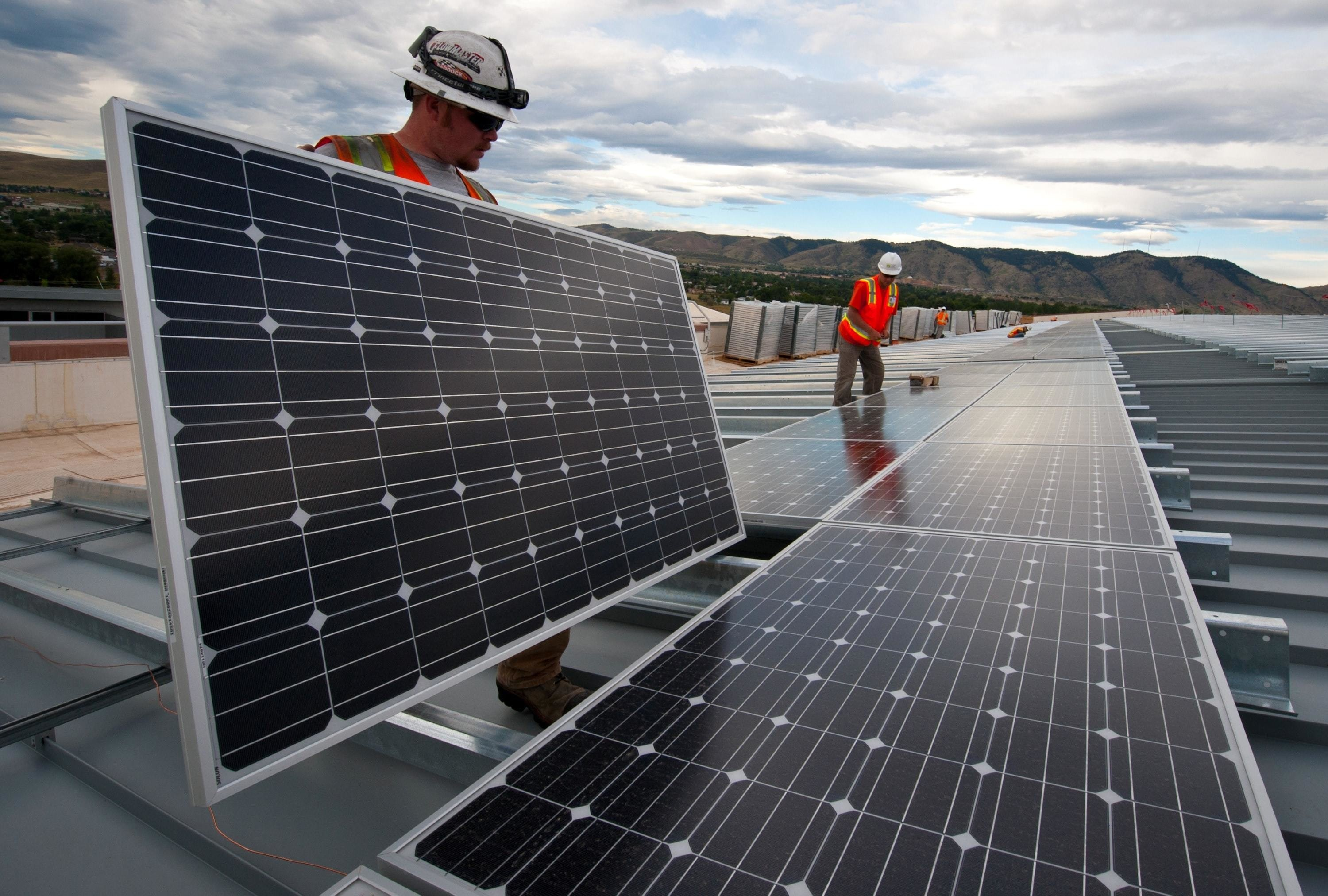 image of 2 men installing solar panels in the U.S. A successful transition to a green economy is possible, but not without proactive planning and open dialogues with workers and communities impacted by the shift