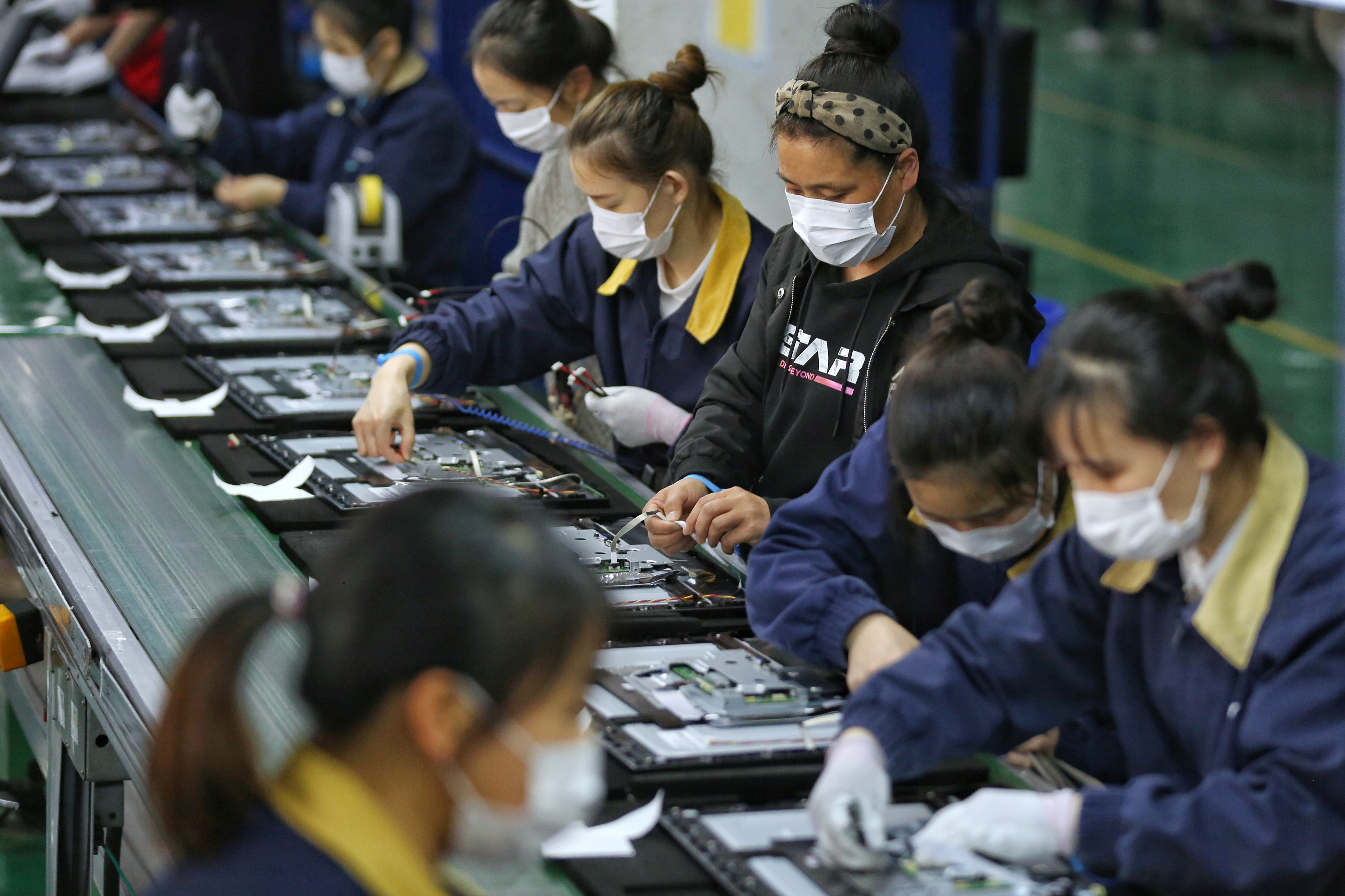 Employees, wearing masks, work on a production line manufacturing display monitors at a TPV factory in Wuhan, Hubei province, the epicentre of the novel coronavirus disease (COVID-19) outbreak in China, April 7, 2020. China Daily via REUTERS  ATTENTION EDITORS - THIS IMAGE WAS PROVIDED BY A THIRD PARTY. CHINA OUT. - RC2LZF9Q7S68