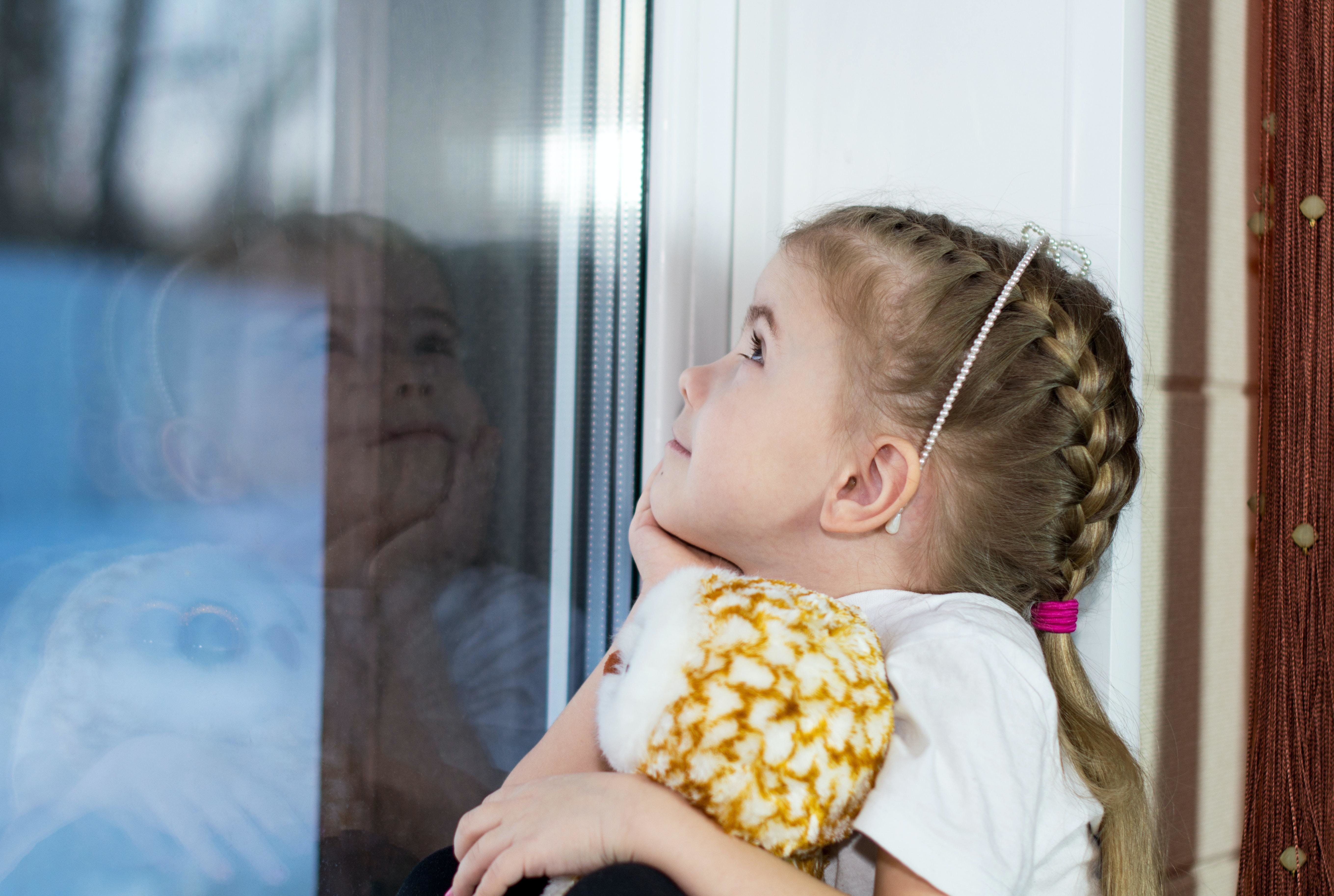 A little girl looking out of the window, lost in a daydream.