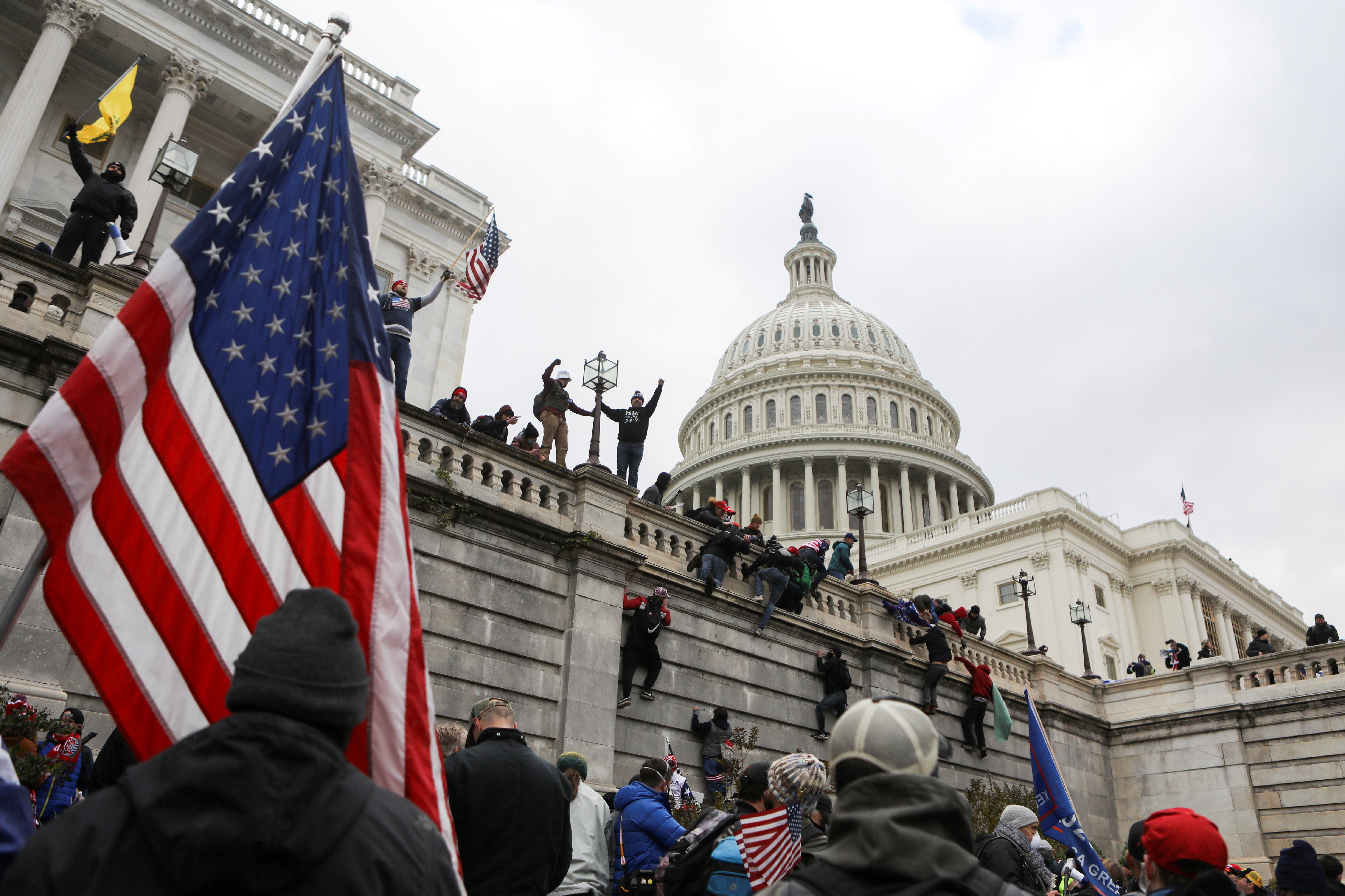 Supporters of U.S. President Donald Trump climb on walls at the U.S. Capitol during a protest against the certification of the 2020 U.S. presidential election results by the U.S. Congress, in Washington, U.S., January 6, 2021. REUTERS/Jim Urquhart     TPX IMAGES OF THE DAY - RC2L2L9T7RPX