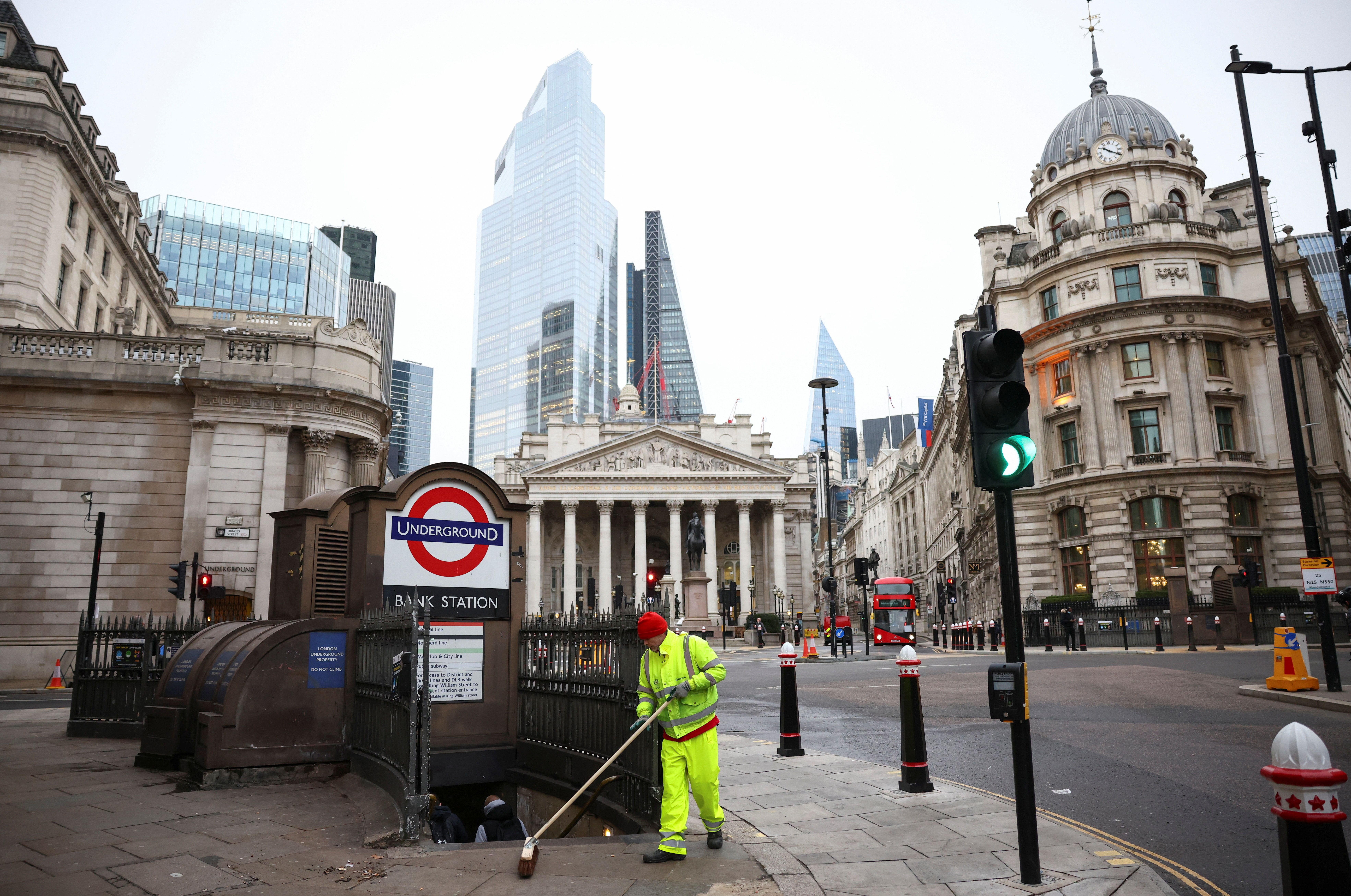 A worker sweeps a pavement at an empty Bank Junction, amid the coronavirus disease outbreak, in London, Britain.