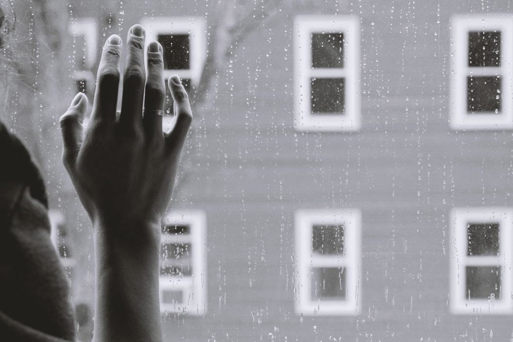 A person rests their hand on the window whilst looking outside.