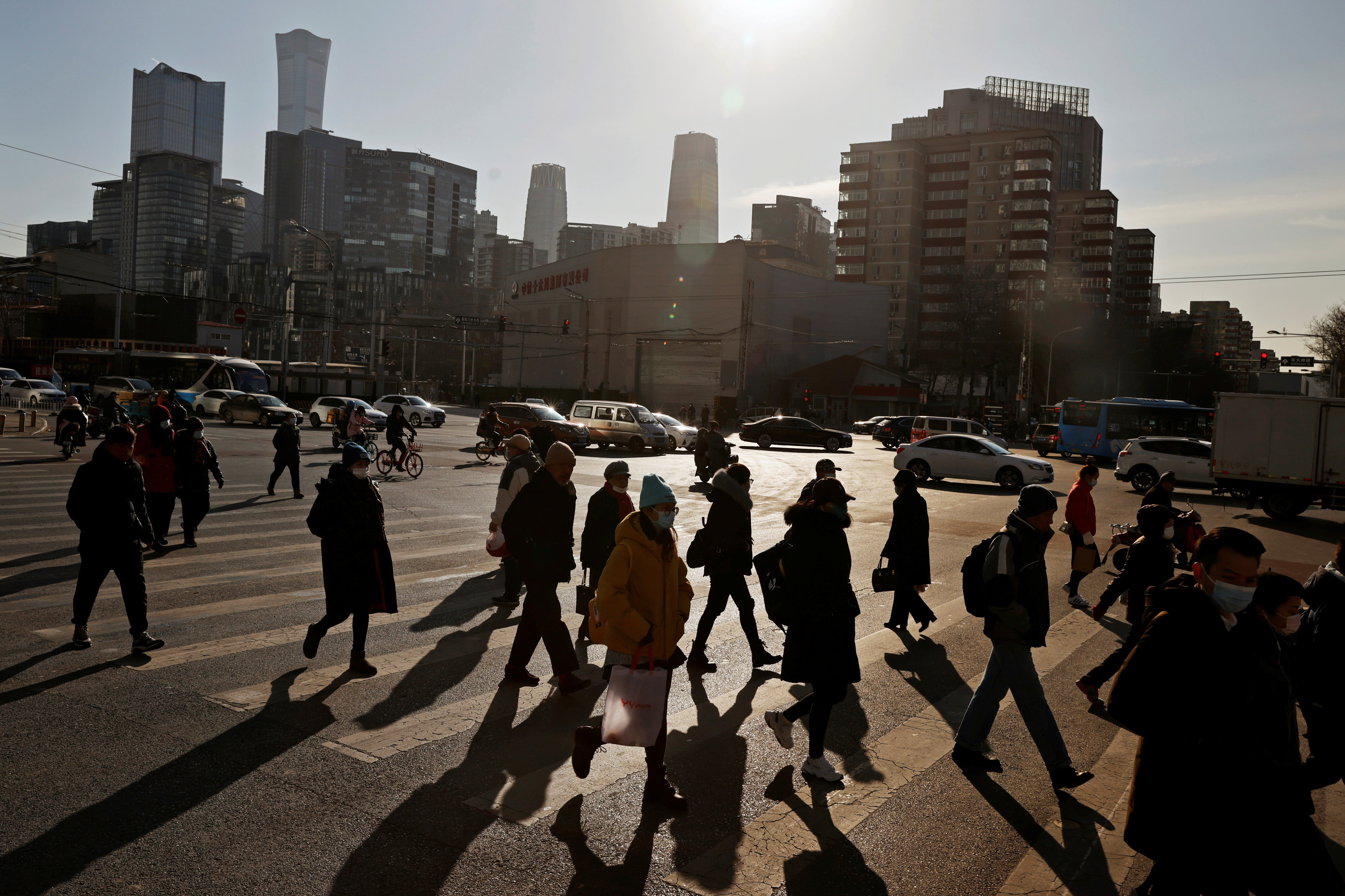 People cross a street during morning rush hour in front of the skyline of the central business district in Beijing, China.