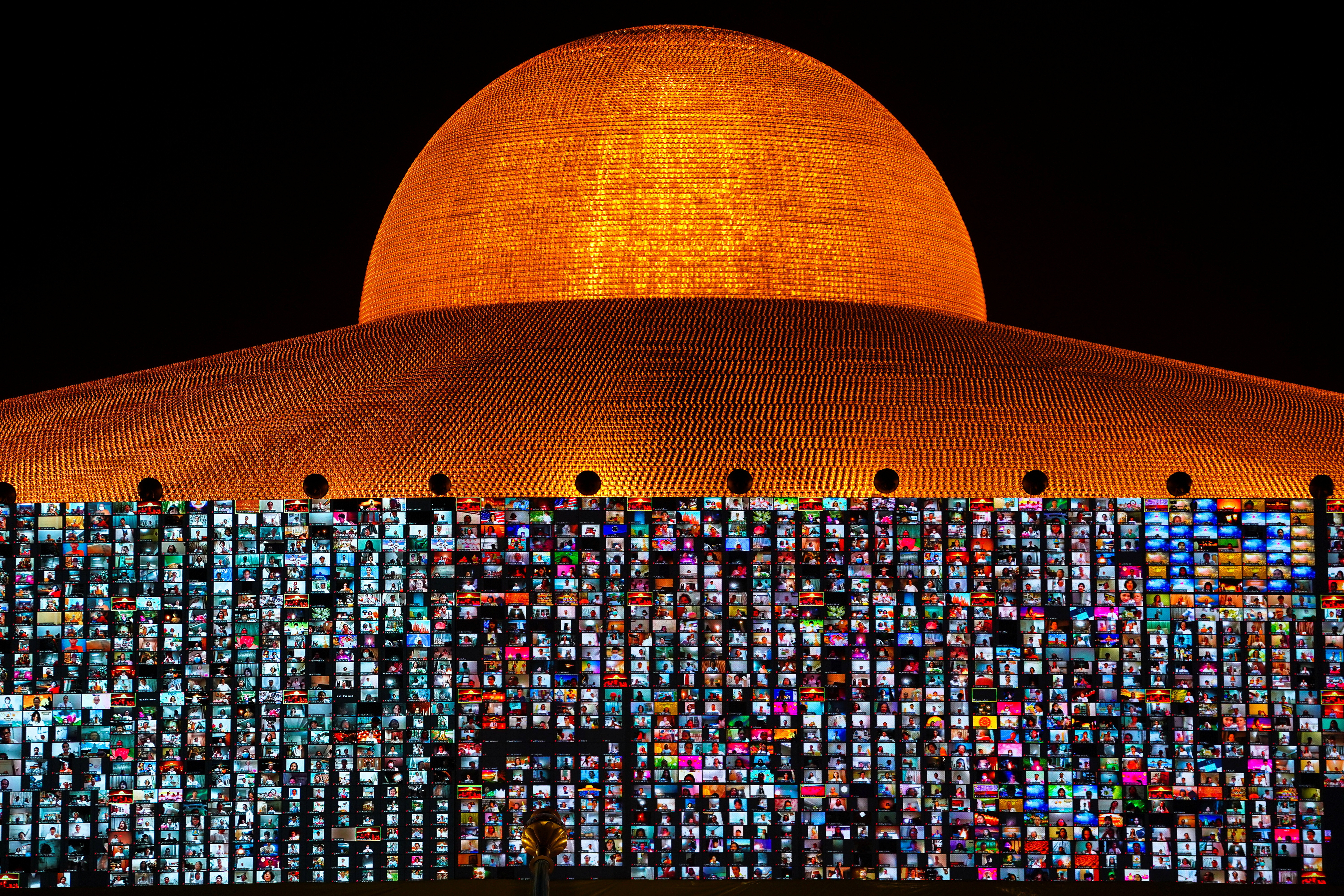 Screens show devotees gathering via the Zoom application during Vesak Day, an annual celebration of Buddha's birth, enlightenment, and death at the Dhammakaya temple amid the coronavirus disease (COVID-19) pandemic in Pathum Thani province, Thailand, May 26, 2021. REUTERS/Athit Perawongmetha - RC2ONN97XM0J