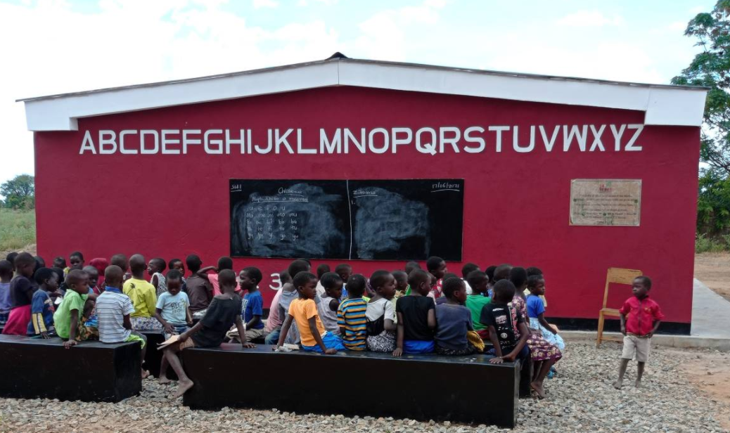 students are seen sitting on benches outside the newly opened 3D-printed school, which was built in 15 hours, in Salima, Malawi