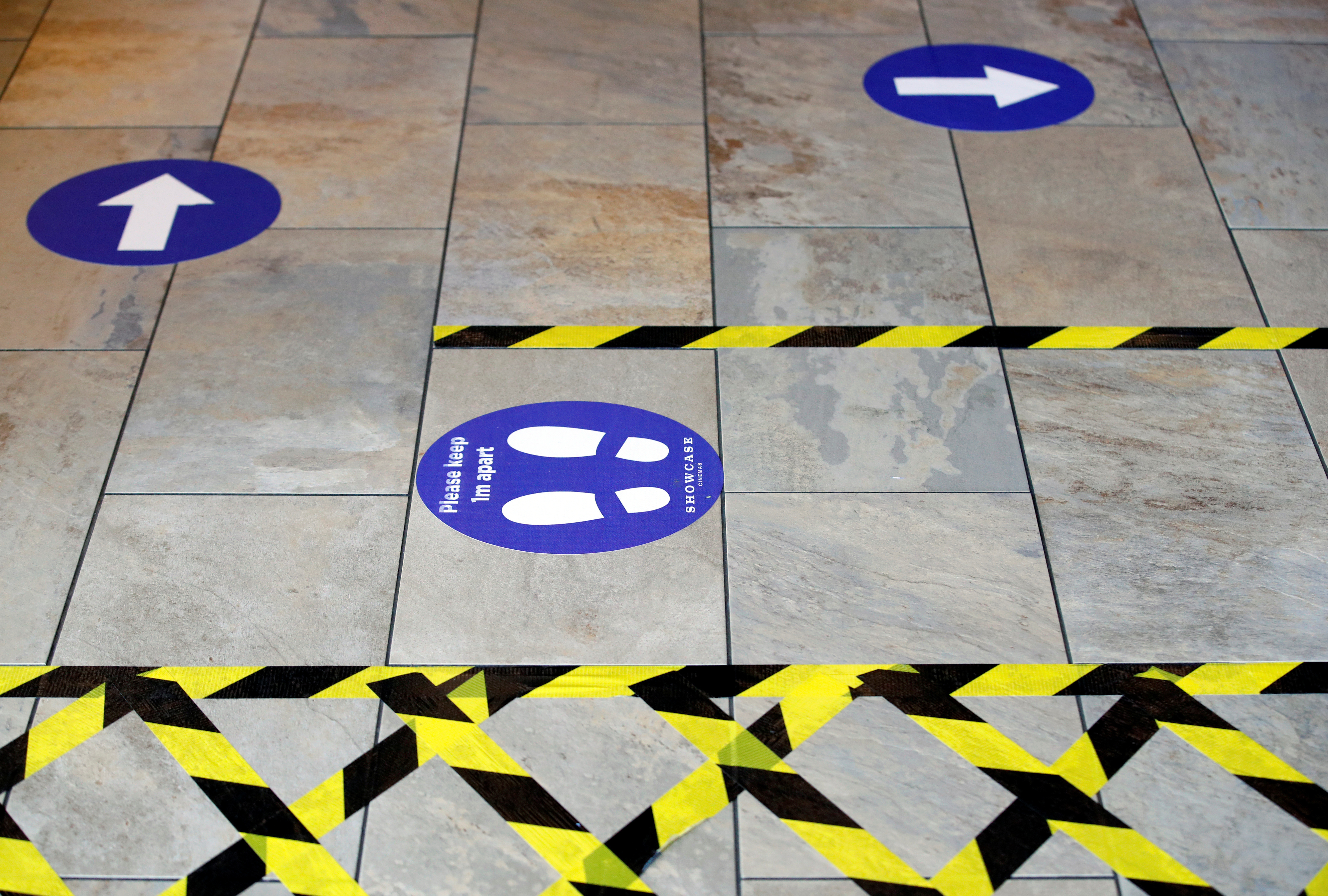 A social distancing sign and markers are pictured on the floor